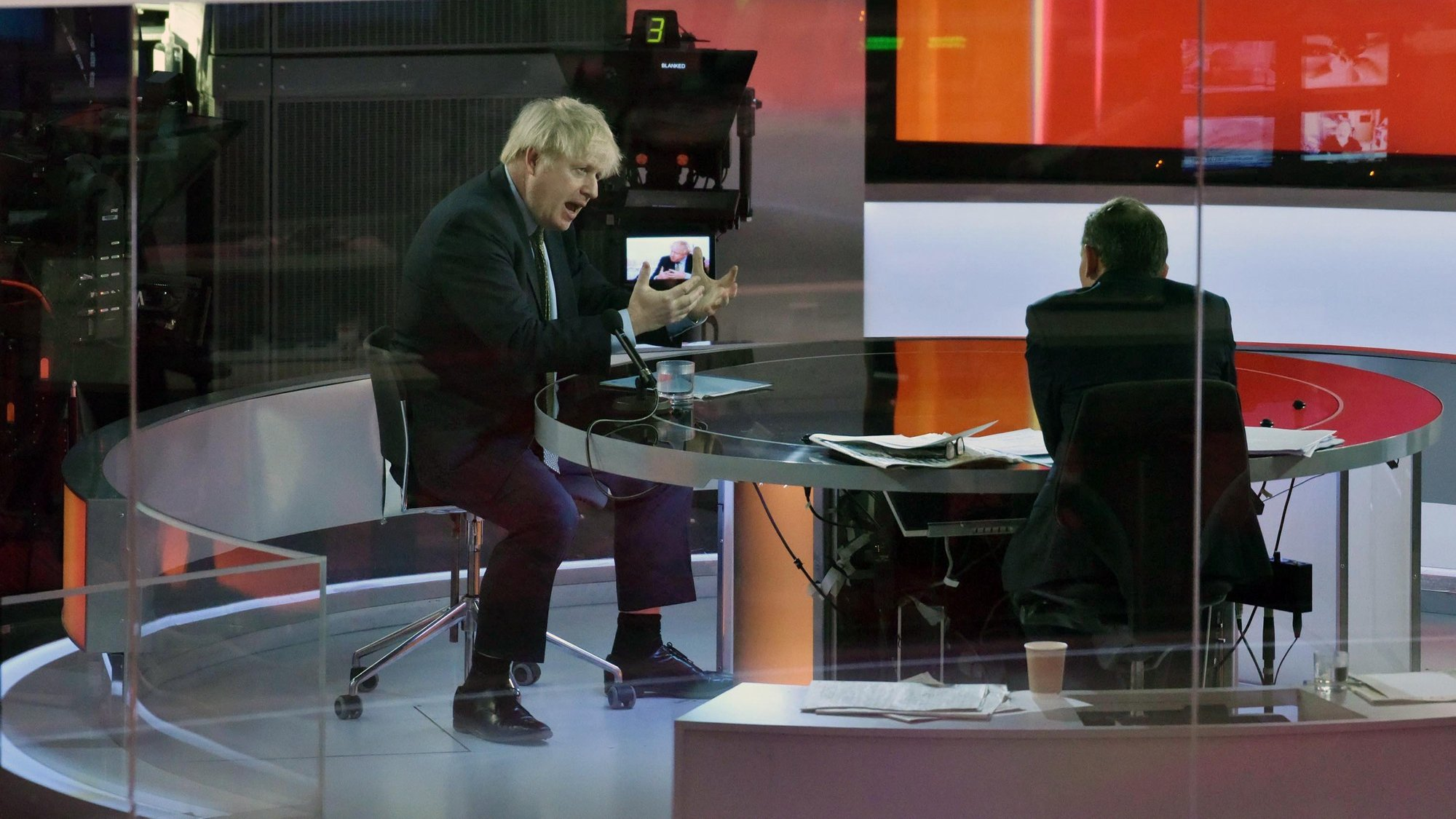 epa08916423 A handout photo made available by the British Broadcasting Corporation (BBC) shows Britain's Prime Minister Boris Johnson appearing at the Andrew Marr show in the BBC studios in London, Britain, 03 January 2021. Johnson said during the interview that Boris Johnson told the BBC that Britain may be facing tougher measures in weeks ahead as the nation battles the ongoing COVID-19 coronavirus pandemic.  EPA/JEFF OVERS HANDOUT ATTENTION EDITORS: PICTURE TAKEN THROUGH GLASS HANDOUT EDITORIAL USE ONLY/NO SALES