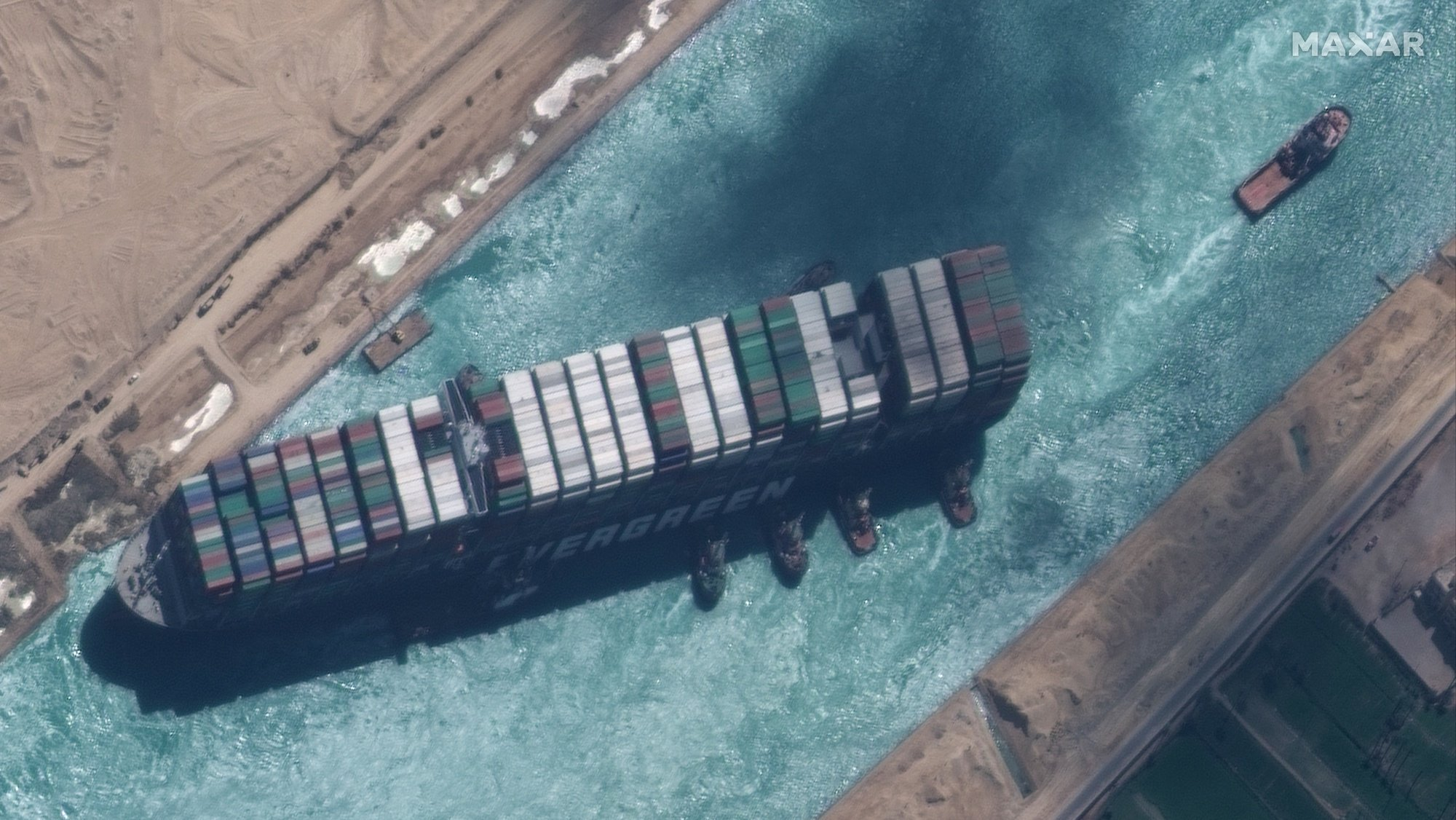 epa09105214 A handout satellite image made available by MAXAR Technologies shows , the Ever Given container ship after it has been moved away from the eastern bank of the canal and tugboats trying to reposition the ship, in the Suez Canal, Egypt, 29 March 2021. The head of the Suez Canal Authority announced on 29 March that the large container ship, which ran aground in the Suez Canal on 23 March, is now free floating after responding to the pulling maneuvers.  EPA/MAXAR TECHNOLOGIES HANDOUT MANDATORY CREDIT: SATELLITE IMAGE 2020 MAXAR TECHNOLOGIES -- the watermark may not be removed/cropped -- HANDOUT EDITORIAL USE ONLY/NO SALES HANDOUT EDITORIAL USE ONLY/NO SALES