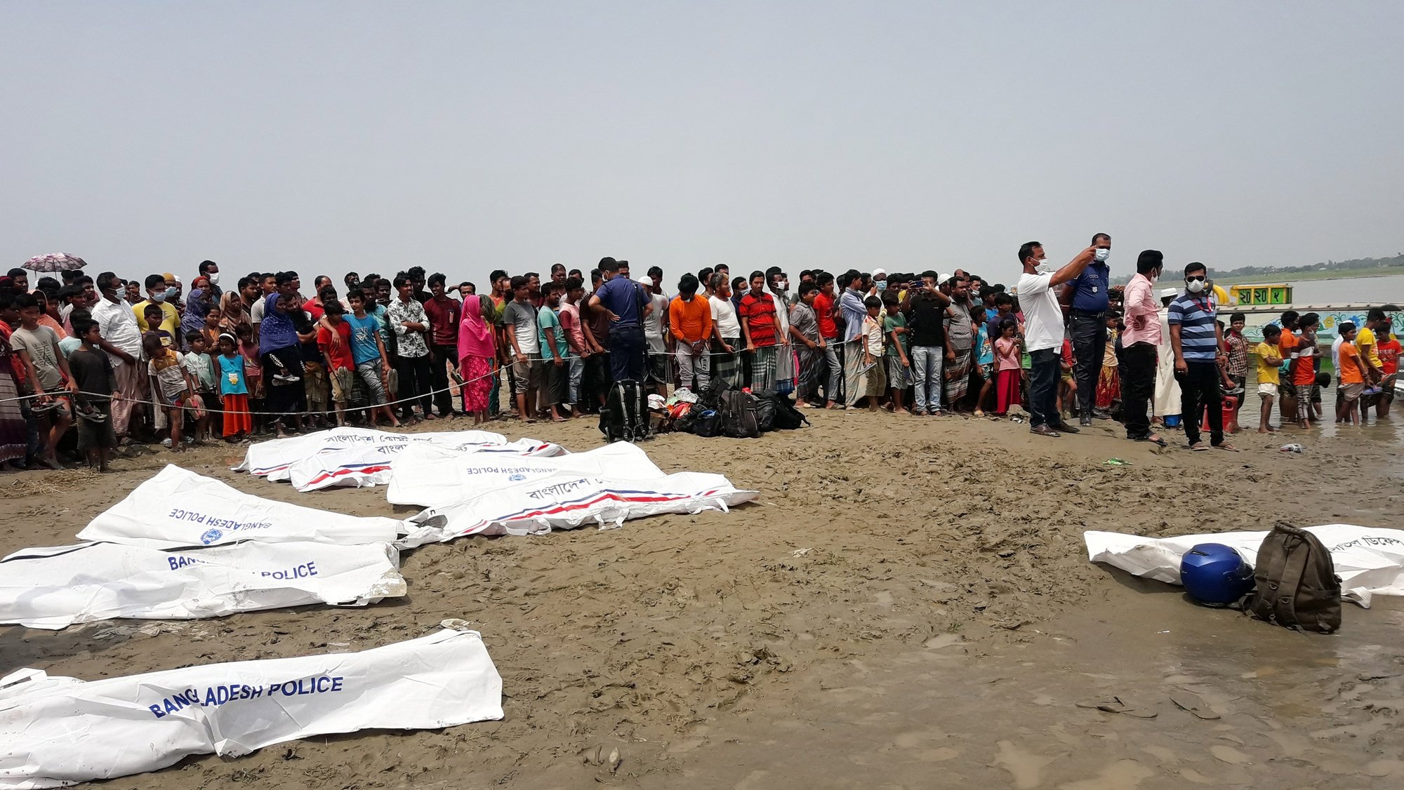 epa09175113 Local people stand by the river as they look at rescue workers lay out the bodies recovered from the river in body bags after a speedboat collided with another boat in the Padma River in Madaripur District,  Bangladesh, 03 May 2021. Local police said at least 26 people were killed and several others went missing after the incident.  EPA/STR