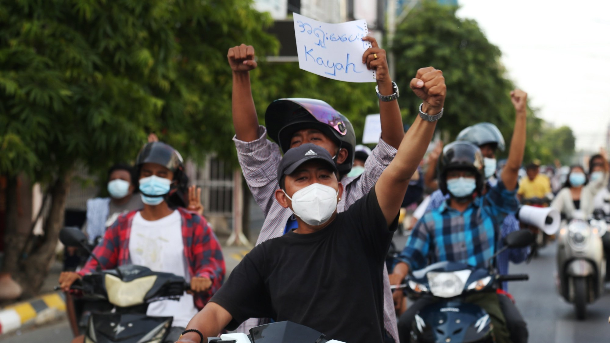 epa09217702 Demonstrators gesture and hold a placard reading 'Don't surrender, Kayah' while riding on motorcycles during a protest against the military coup in Mandalay, Myanmar, 21 May 2021. At least 800 people have been killed by Myanmar armed forces and more than 4,000 detained since the military seized power on 01 February 2021, according to the Assistance Association for Political Prisoners (AAPP).  EPA/STRINGER