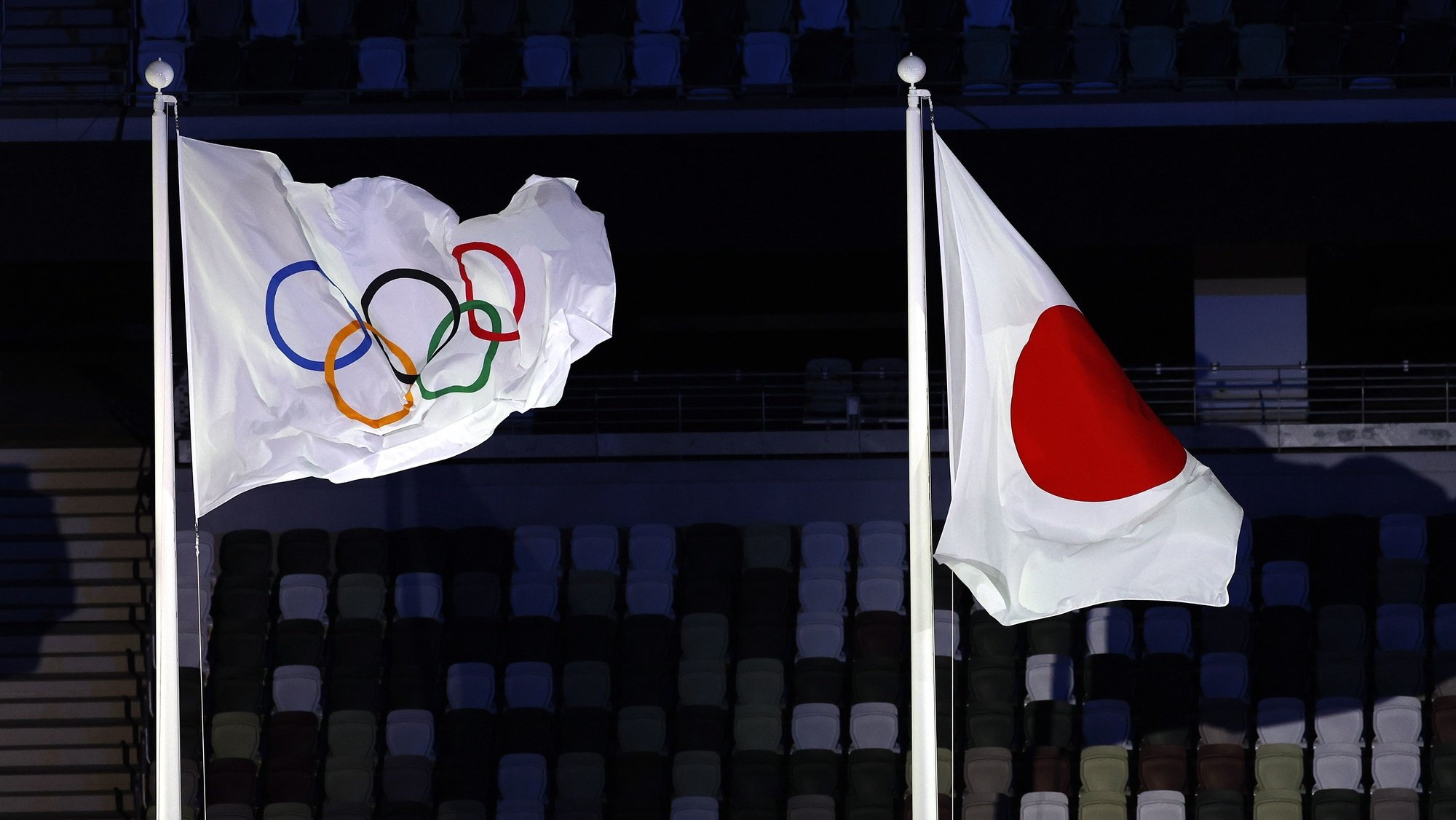 epa09360022 The Olympic flag flies next to the Japanese flag during the Opening Ceremony of the Tokyo 2020 Olympic Games at the Olympic Stadium in Tokyo, Japan, 23 July 2021.  EPA/RUNGROJ YONGRIT