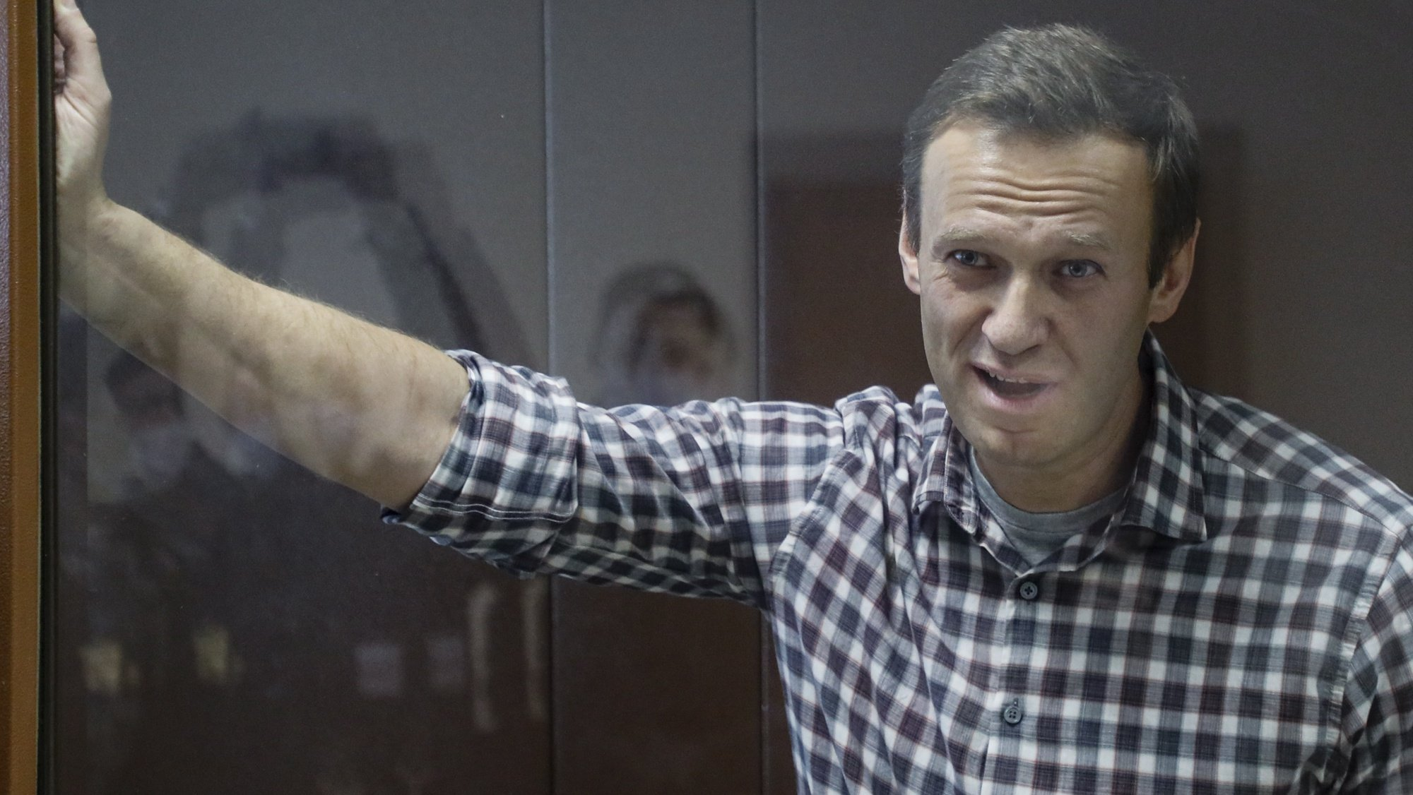 epa09025250 Russian opposition leader Alexei Navalny stands inside a glass cage prior to a hearing at the Babushkinsky District Court in Moscow, Russia, 20 February 2021. The Moscow City court will hold a visiting session at the Babushkinsky District Court Building to consider Navalny's lawyers appeal against a court verdict issued on 02 February 2021, to replace the suspended sentence issued to Navalny in the Yves Rocher embezzlement case with an actual term in a penal colony.  EPA/YURI KOCHETKOV MANDATORY CREDIT