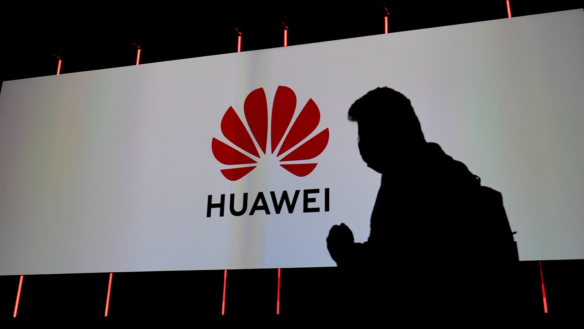 epa08643887 Silhouette of visitor next to the logo of Huawei displayed on a screen at the Huawei stand at the International Consumer Electronics Fair (IFA) in Berlin, Germany, 03 September 2020. The IFA. the world's leading trade show for consumer electronics and home appliances. runs from 03 to 06 September 2020.  EPA/FILIP SINGER