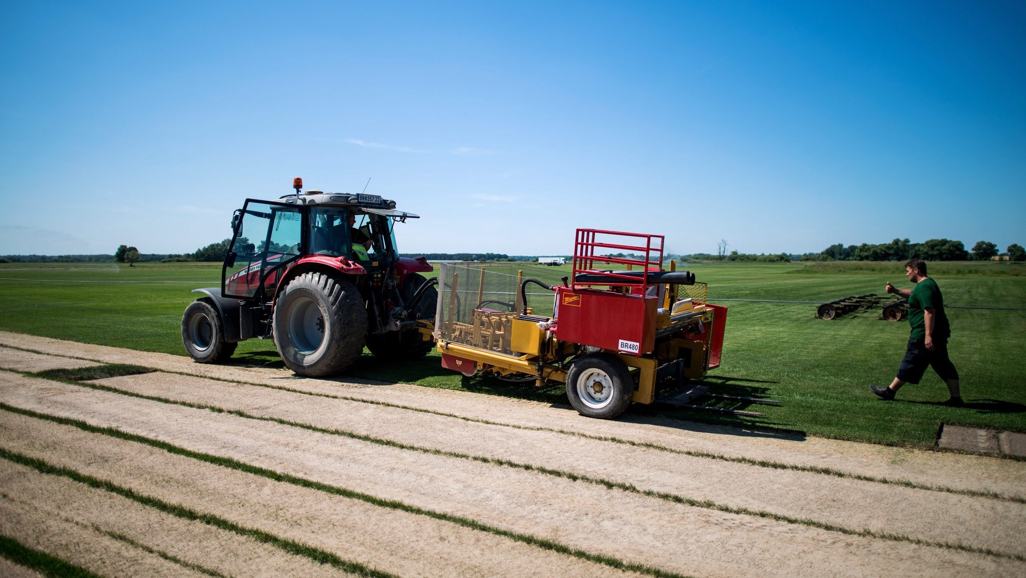 epa05350602 A tractor with a harvester is seen on a sports turf field of turf manufacture Richter Lawn near Zavod, Slovakia, on 07 June 2016. Austrian family business run by the fifth generation, Richter Lawn grows natural turf in Austria and Slovakia. Their special stadium turf lawn, grown on silica sand natural soil, was sodded for the UEFA Champions League Final 2015 in Berlin, Germany, the EURO 2012 in Kiev, Lviv and Donetsk, Ukraine and the EURO 2016 in Nice, Lille and Marseille, France.  EPA/CHRISTIAN BRUNA