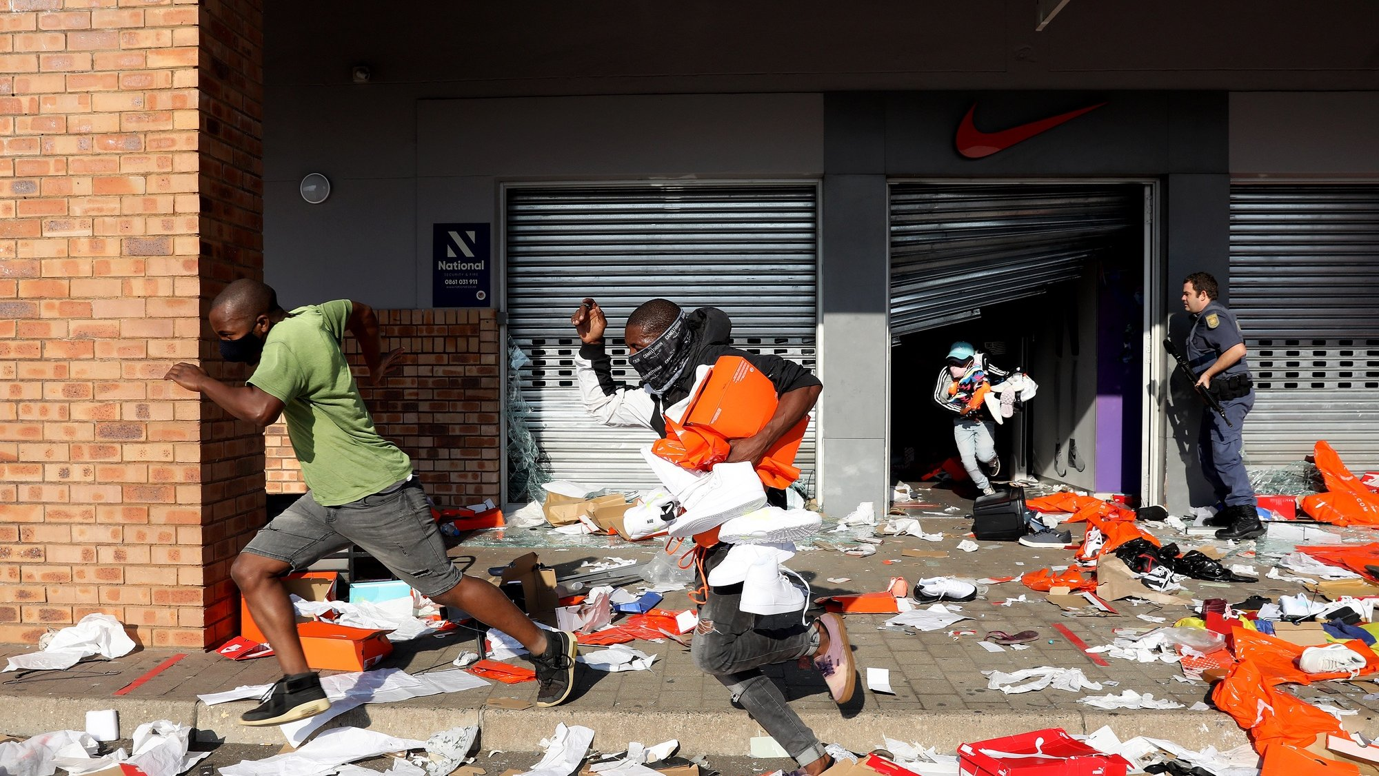 epaselect epa09340528 Looters empty a store of goods in the Springfield Value Centre during protest in, Durban, South Africa, 12 July 2021. Former South Africa President Zuma was arrested on 07 July, and sentenced to 15 months in prison for contempt of court. Protests by his supporters included shops being looted, burned cars and the blocking of city streets in the country.  EPA/STR