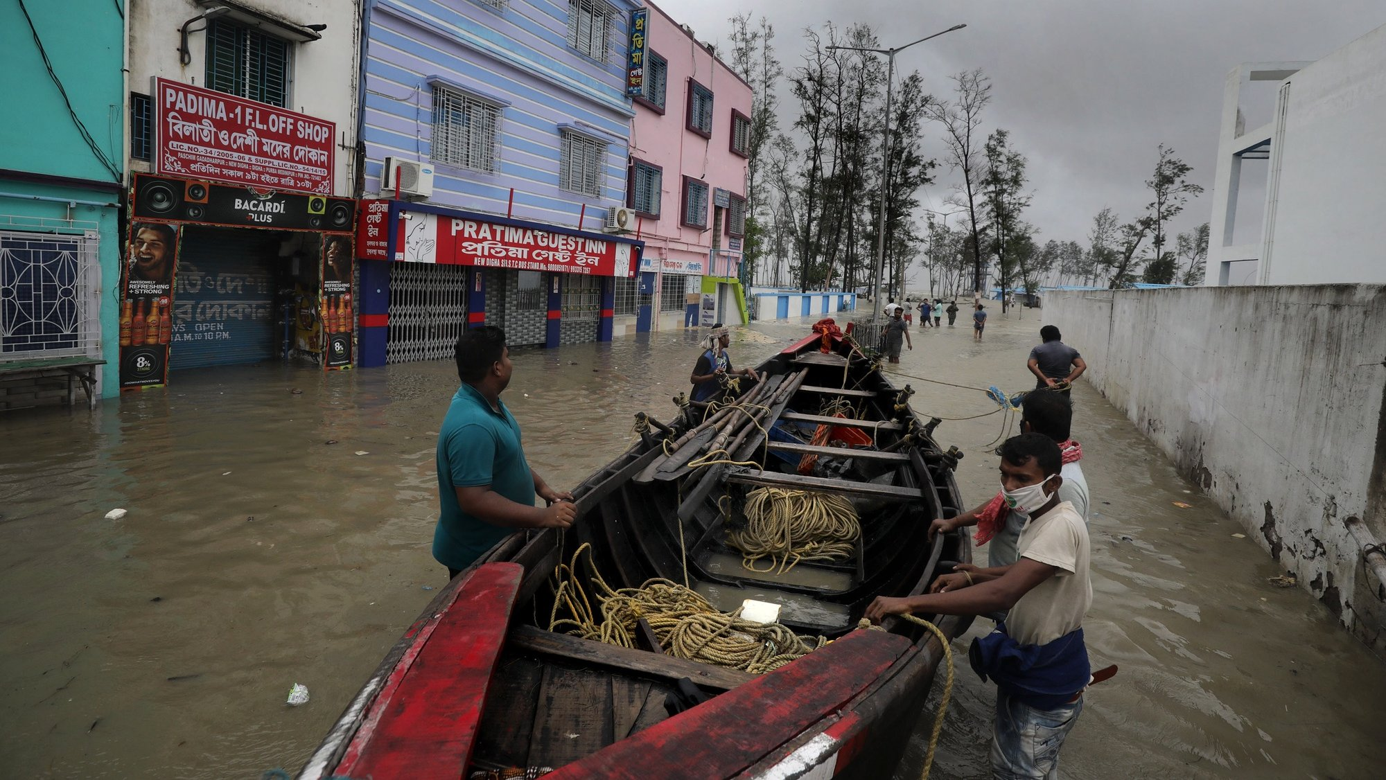 epa09228287 Villagers prepare a boat to rescue people amid a flood as Cyclone Yaas makes landfall in Digha, near the Bay of Bengal, south of Kolkata, India, 26 May 2021. The Odisha and Bengal governments started the evacuation of at-risk areas, as Cyclone Yaas hits the eastern coast of India.  EPA/PIYAL ADHIKARY