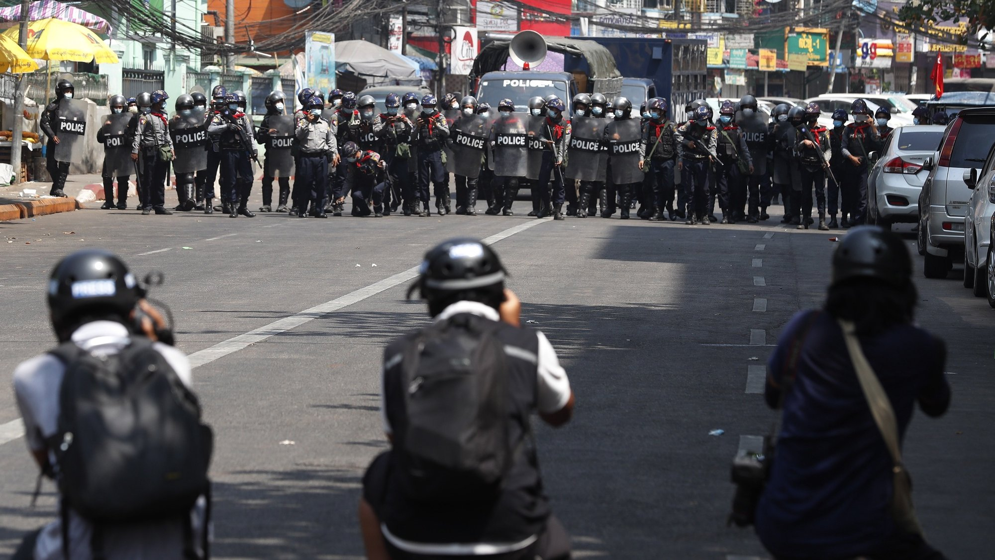 epa09037447 Riot police advance on a street as members of the press take photos during a protest against the military coup, in Yangon, Myanmar, 26 February 2021 Anti-coup protests continue in Myanmar amid regional diplomatic attempts to reach a resolution to weeks of unrest caused by the military coup.  EPA/NYEIN CHAN NAING