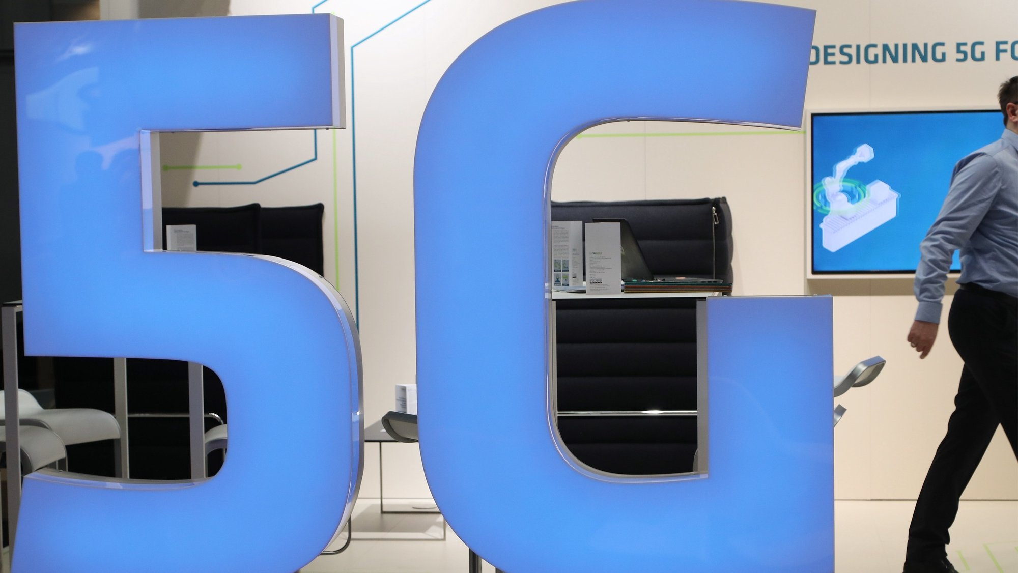 epa07475973 A man walks  behind a 5G logo at the Hannover Industry Fair (Hannover Messe) in Hanover, Germany, 31 March 2019. From 01 April to 05 April, 6,500 exhibitors from 75 countries show their products during one of the World's leading fairs for industrial goods. Main focus of the Hannover Messe 2019 is on Artificial Intelligence and the new mobile standard 5G.  EPA/FOCKE STRANGMANN