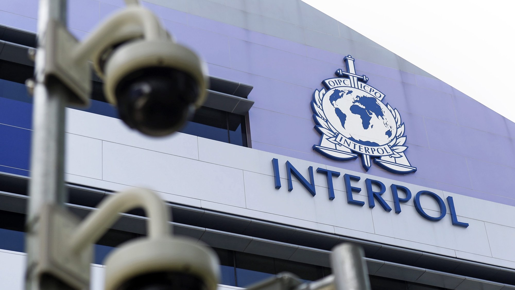 epa04703664 Security cameras pictured against the Interpol logo on the Interpol Global Complex for Innovation building (IGCI) in Singapore, 14 April 2015. Interpol's first digital crime centre was officially opened in Singapore on 13 April 2015. Complementing its headquarters in Lyon, the Interpol Global Complex for Innovation (ICGI) will support international policing efforts against cybercrime, as well as research and capacity building in online security.  EPA/WALLACE WOON