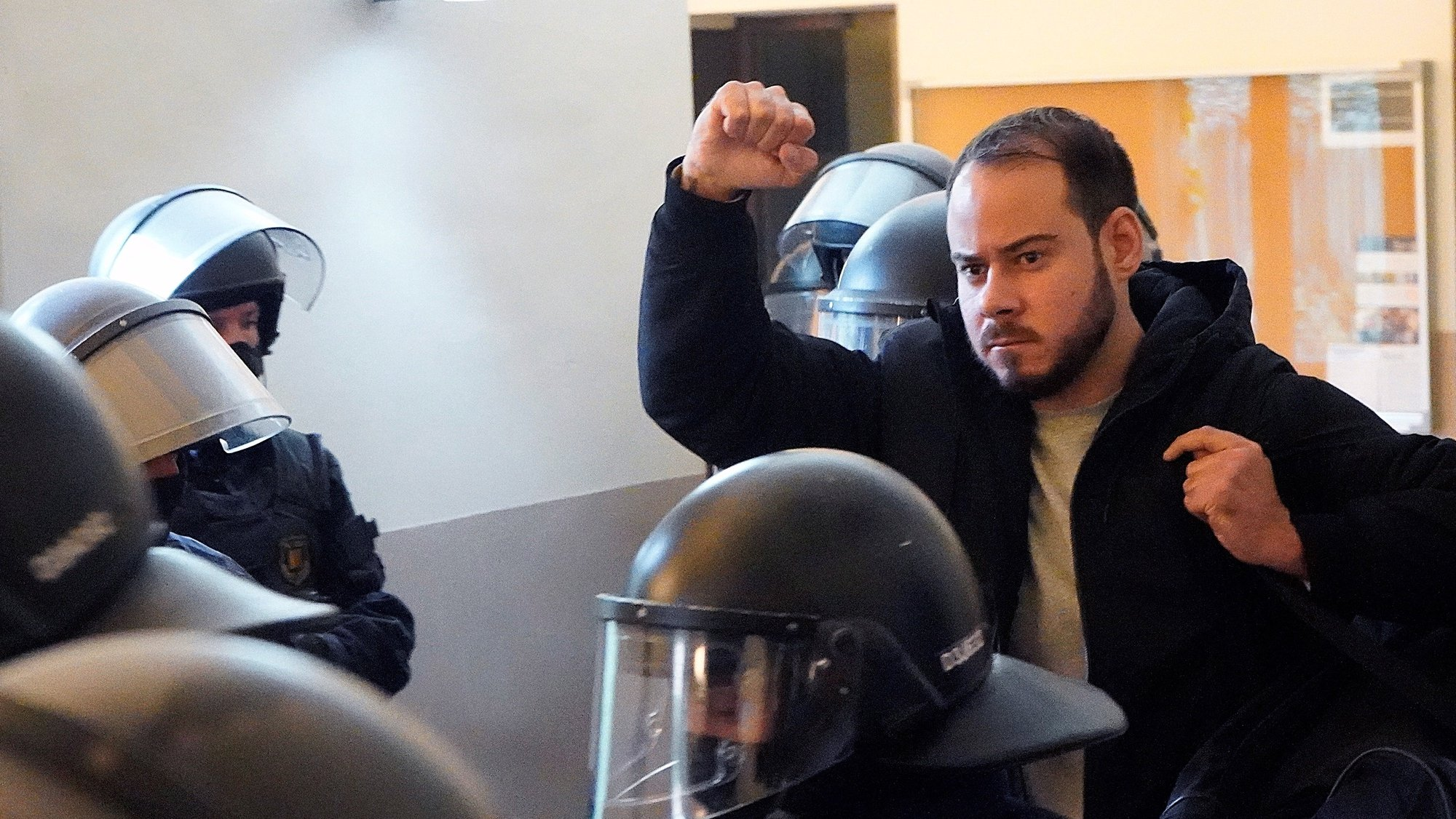 epa09015946 Spanish rapper Pablo Hasel raises his fist as he is arrested by Mossos d'Esquadra police inside Lleida University after the deadline of his voluntary entry to prison has passed, in Lleida, Catalonia, Spain, 16 February 2021. Hasel was sentenced to a nine months in jail late January after the Supreme Court found him guilty of glorifying terrorism and insulting the crown and state institutions, triggering rallies of Rights Associations demanding free speech and for the government political parties (Unidas Podemos and Socialist Partty) to reform the criminal code for crimes involving freedom of expression.  EPA/Paul de la Calle