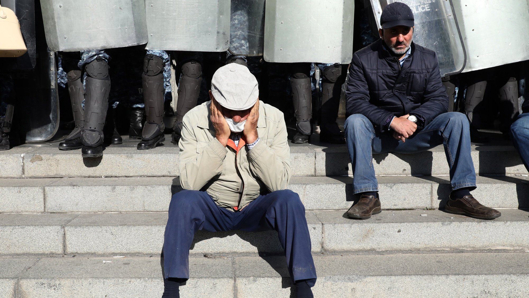 epa08813457 Armenian men sit in front of a police cordon during an opposition rally in Yerevan, Armenia, 11 November 2020. Protesters demand the resignation of Armenian Prime Minister Nikol Pashinyan and his government. The unrest  and protests erupted in Yerevan on 10 November 2020 after Armenian Prime Minister and Presidents of Azerbaijan and Russia signed a trilateral statement announcing the halt of ceasefire and all military operations in the Nagorno-Karabakh conflict zone.  EPA/STEPAN POGHOSYAN / PHOTOLURE MANDATORY CREDIT