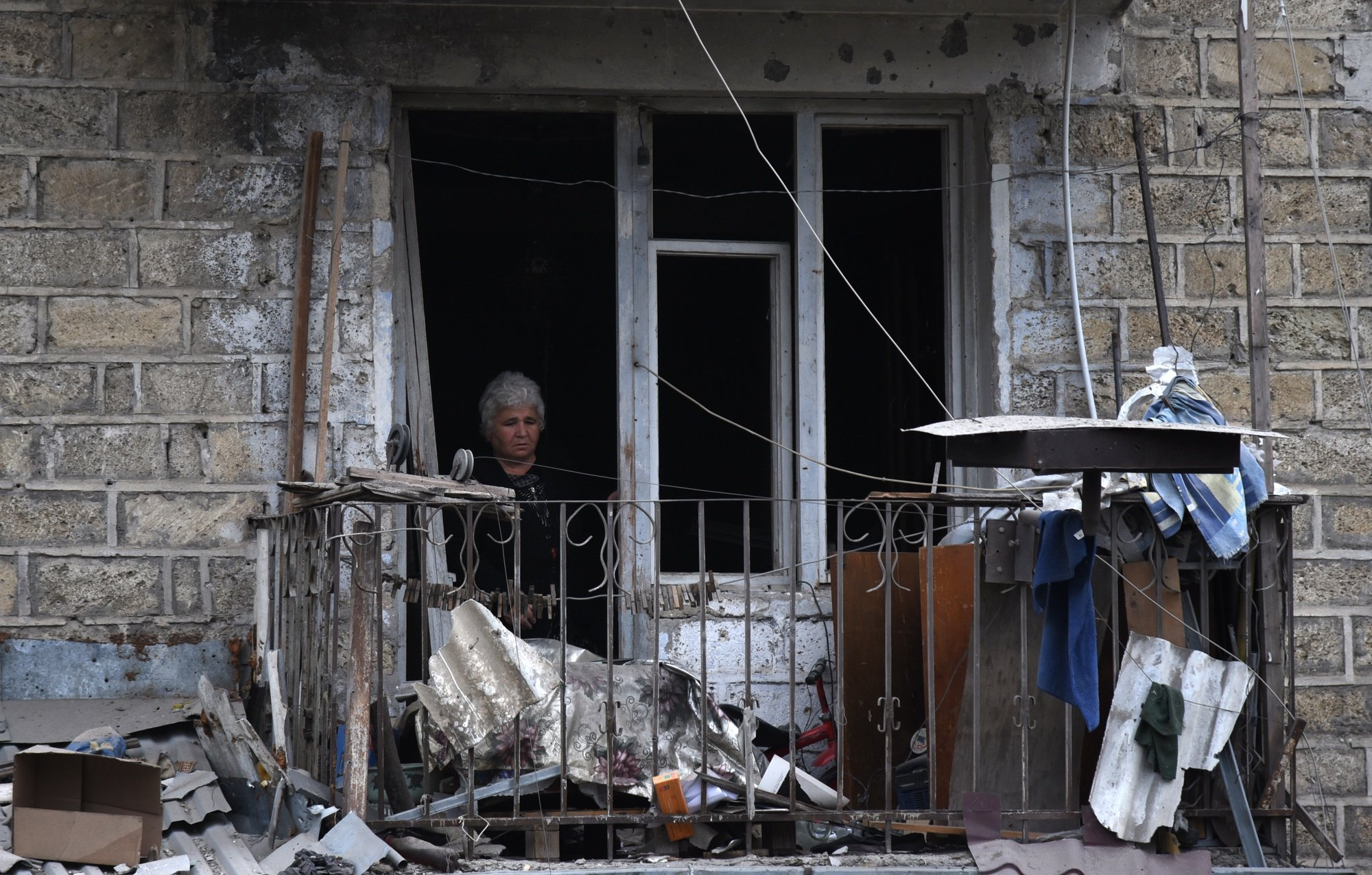 epaselect epa08721179 A woman looks out the window of apartment house after shelling by Azerbaijani artillery, Stepanakert, Nagorno-Karabakh, 04 October 2020. AArmed clashes erupted on 27 September 2020 in the simmering territorial conflict between Azerbaijan and Armenia over the Nagorno-Karabakh territory along the contact line of the self-proclaimed Nagorno-Karabakh Republic (also known as Artsakh).  EPA/DAVID GHAHRAMANYAN / NKR INFOCENTER / PAN PHOTO