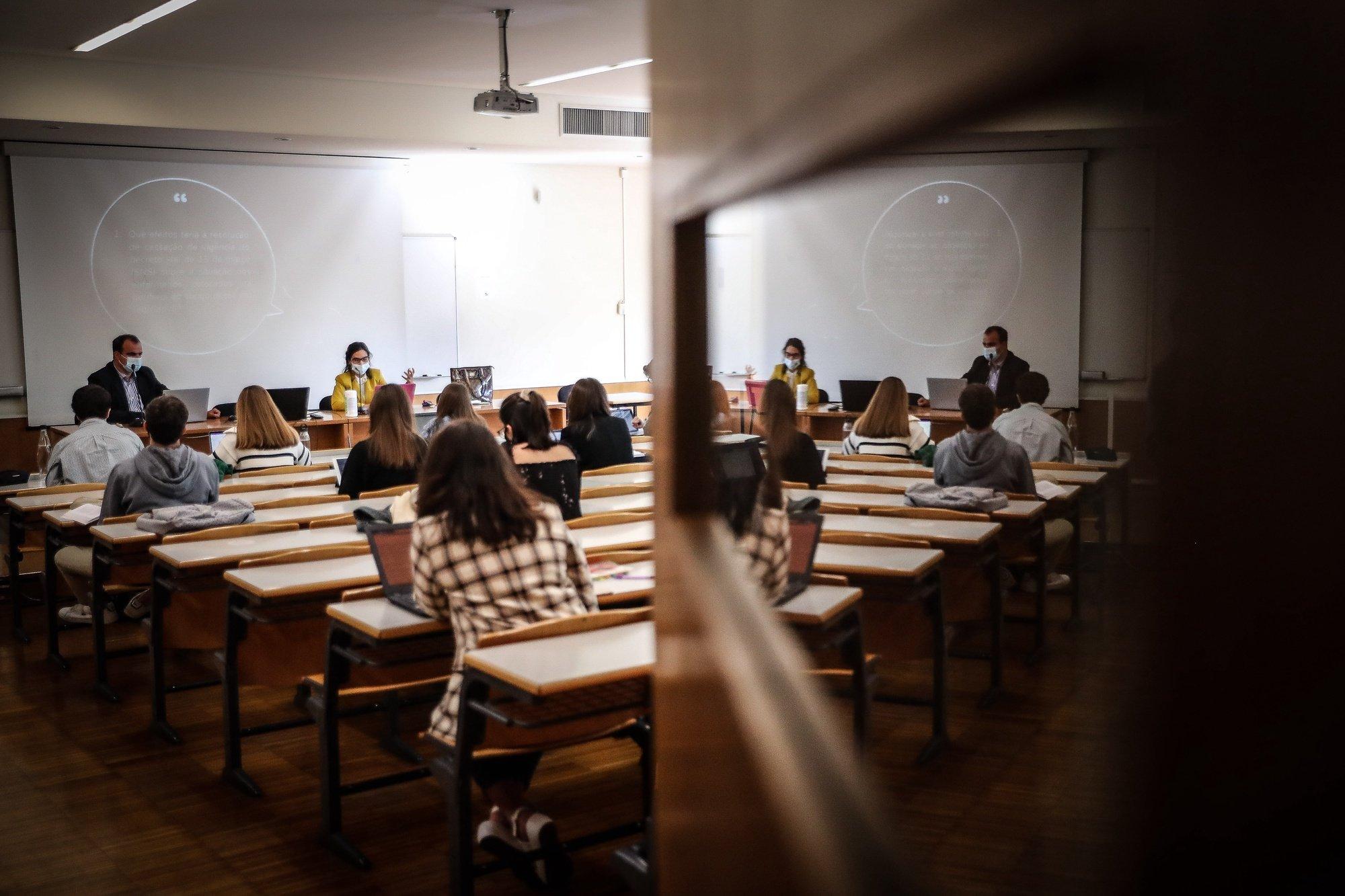 Alunos frequentam uma aula Direito Constitucional no dia do regresso às aulas na Faculdade de Direito da Universidade de Lisboa, no âmbito das novas medidas de desconfinamento relacionadas com a pandemia da covid-19, no Campus de Campolide, em Lisboa, 19 de abril de 2021. Portugal inicia hoje a terceira fase do desconfinamento com a reabertura de mais escolas, lojas, restaurantes e cafés, um levantamento de restrições que não é acompanhado nos 10 concelhos onde a incidência da covid-19 é maior. MÁRIO CRUZ/LUSA