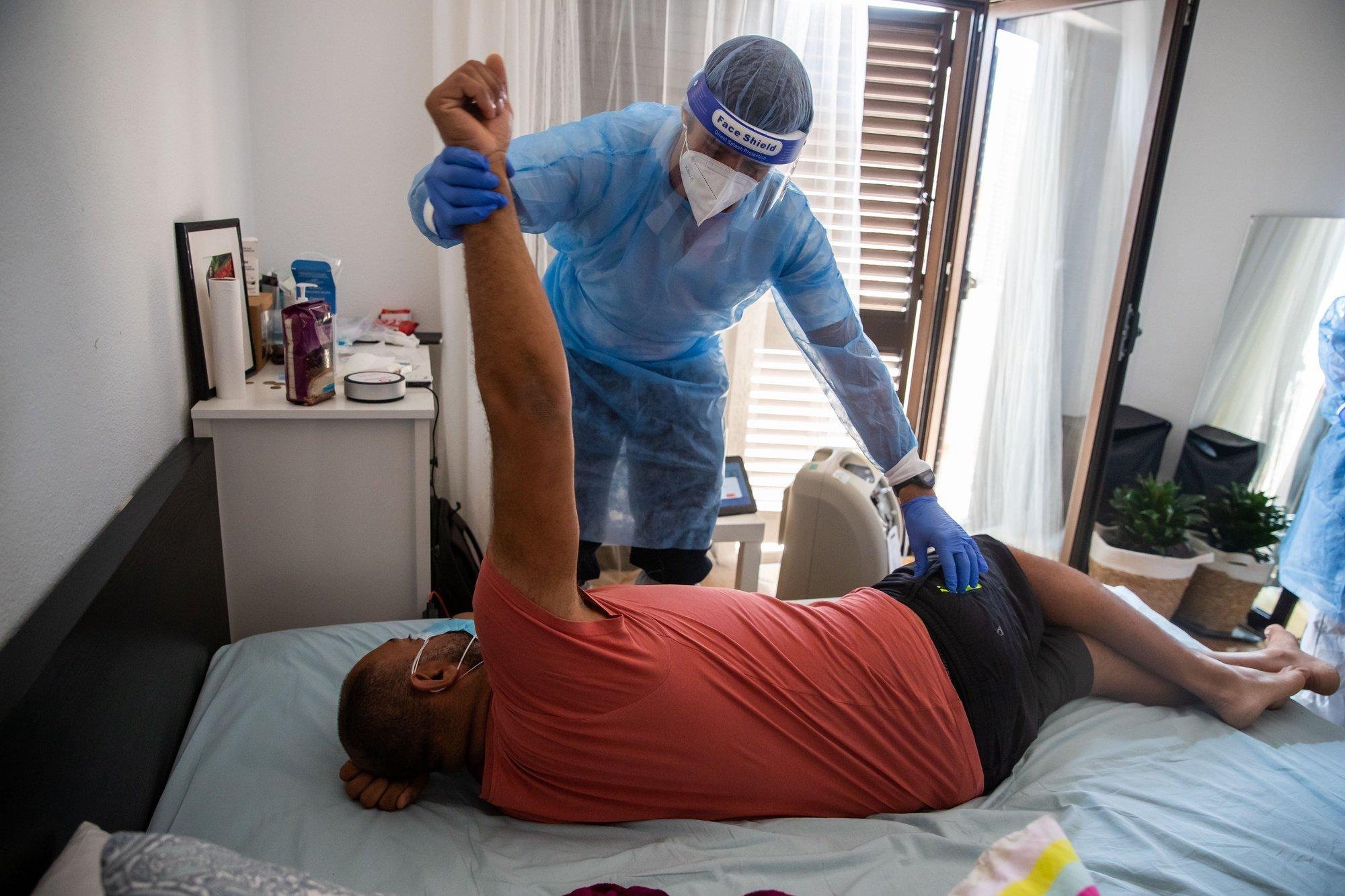 O enfermeiro da Unidade de Hospitalização Domiciliária do Hospital Garcia de Orta, Filipe Dias, ensina exercícios respiratórios a Jair, um paciente internado em casa com Covid-19, na zona do Seixal, 21 de julho de 2021. JOSÉ SENA GOULÃO/LUSA (ACOMPANHA TEXTO DE 24/07/2021)