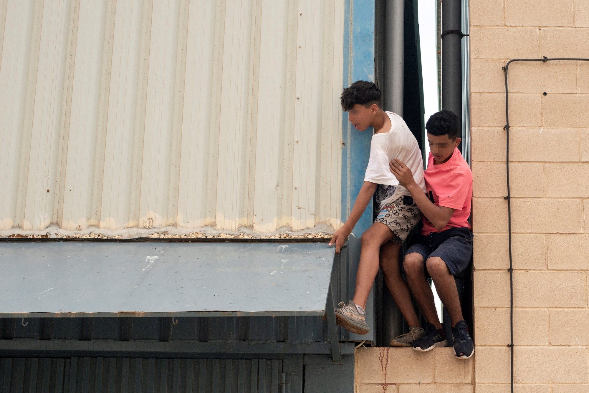 epa09218155 Two underage migrants escape from an industrial estate next to Tarajal beach, in the city of Ceuta, Spanish enclave in northern Africa, 21 May 2021. Local authorities reported that between 8,000-10,000 migrants managed to enter Spain from 18 to 19 May.  EPA/BRAIS LORENZO ATTENTION EDITORS: FACES PIXELATED AT SOURCE DUE TO LEGAL REQUIREMENTS