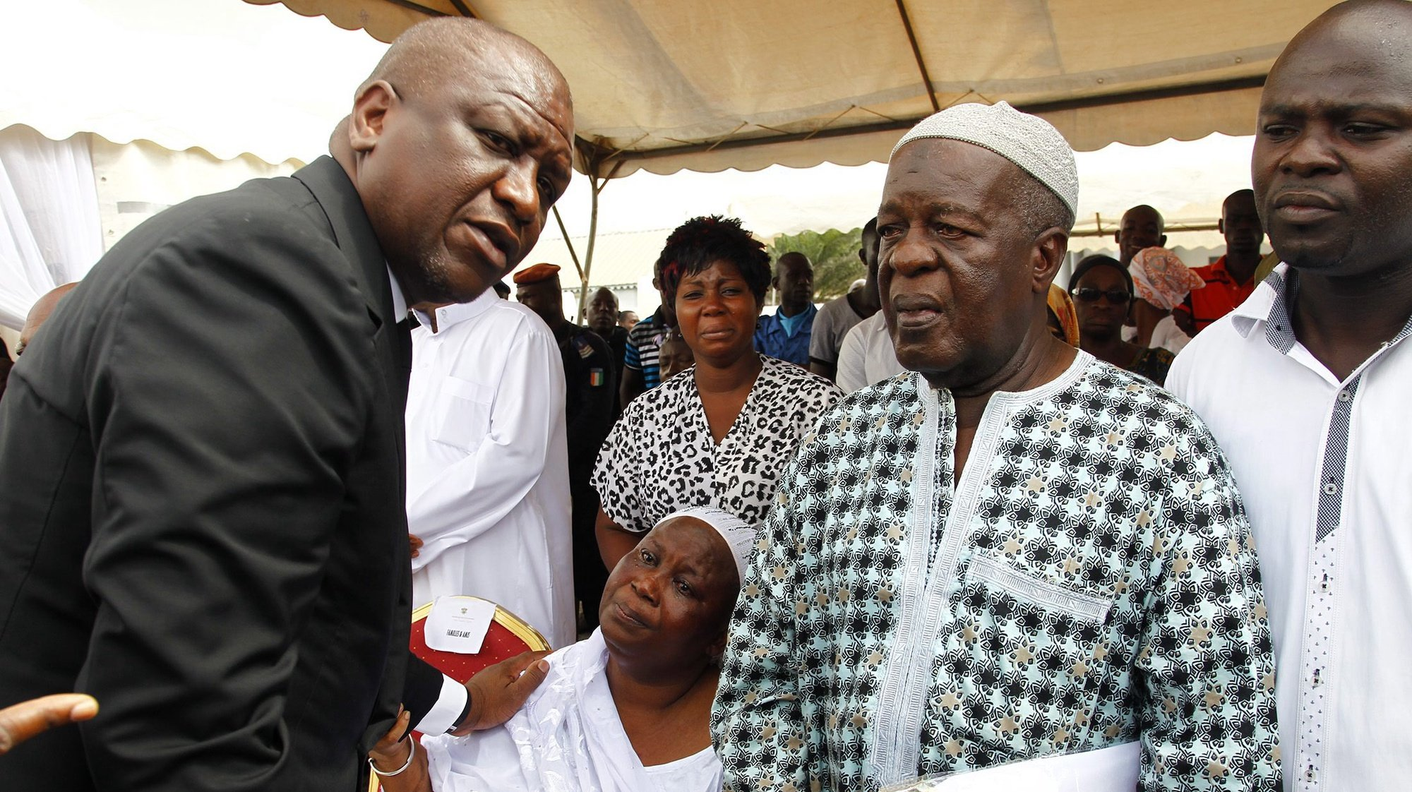 epa05249727 Ivorian minister of security and interior Hamed Bakayoko (L) comforts parents of victims who lost lives in the Grand Bassam beach attack during a ceremony to honour the victims in Abidjan, Ivory Coast, 08 April 2016. According to reports, fourteen civilians and six assailants were killed on 13 March 2016 when gunmen opened fire on guests on the beach at the Etoile du Sud hotel in the town of Grand Bassam which is popular with foreigners. Al-Qaeda in the Islamic Maghreb (AQIM) claimed responsibility for the attack. Among those killed were a French and German national.  EPA/LEGNAN KOULA