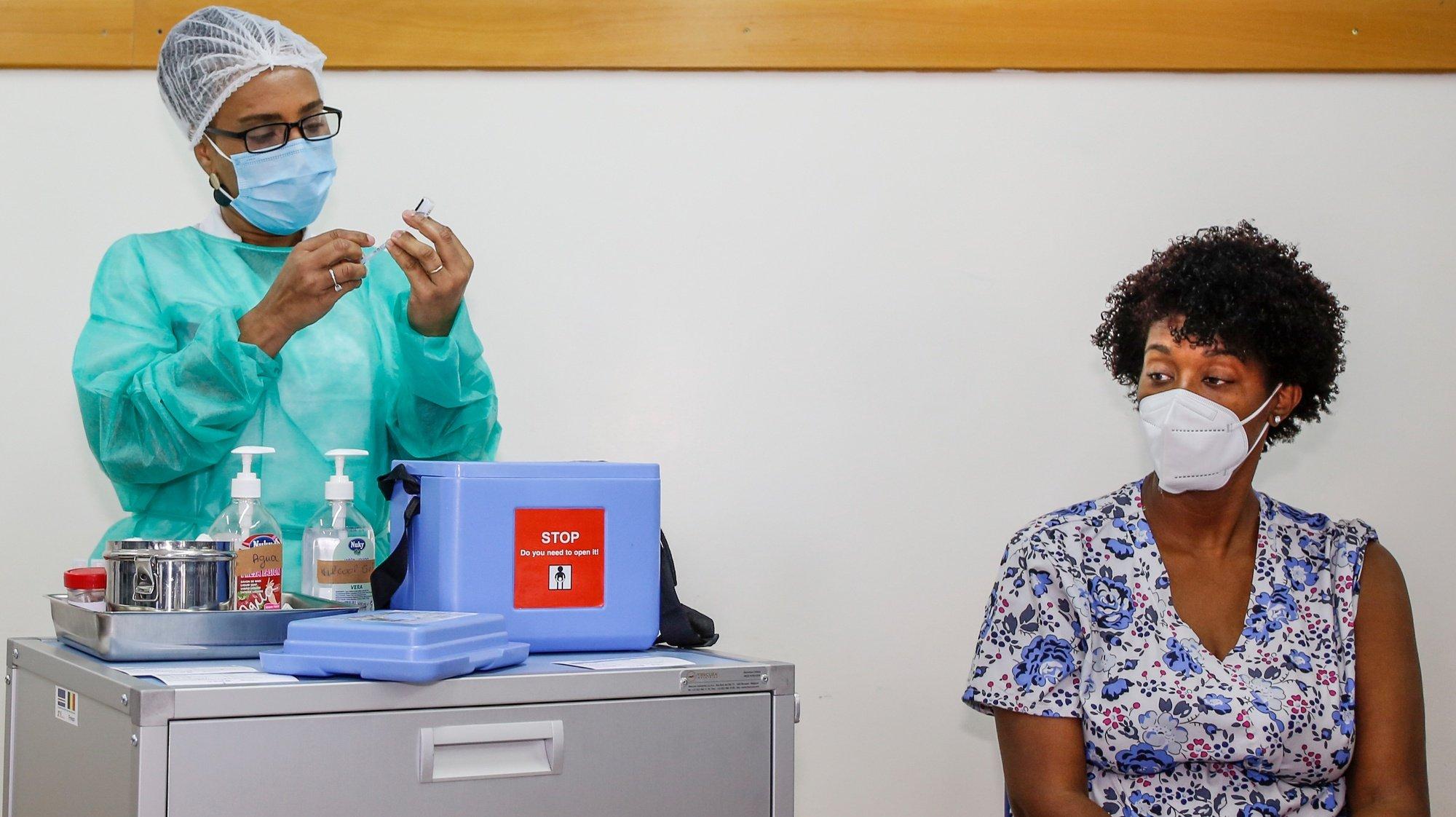 Uma profissional de saúde administra a vacina da Pfizer a covid-19 a um dos seis profissionais de saúde da Praia, antecedendo o início da campanha de vacinação em Cabo Verde, sexta-feira, precisamente um ano depois da chegada da pandemia ao arquipélago, no Centro de Saúde da Achada de Santo António, na Praia, Cabo Verde, 18 de março de 2021. FERNANDO DE PINA/LUSA
