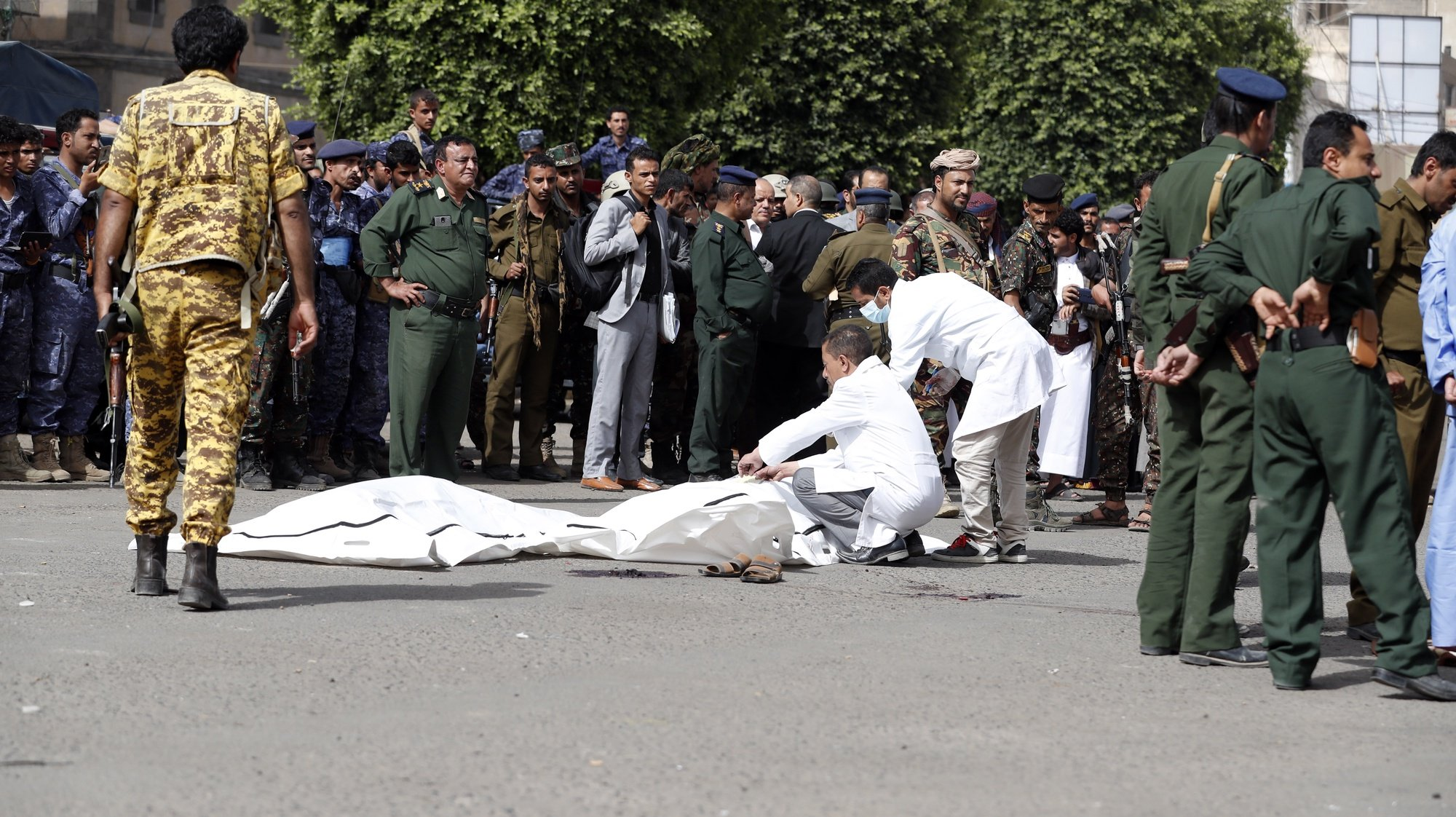 epa09275416 Soldiers wrap the bodies of Abdullah Al-Makhali and Mohammed Arman, convicted of raping and murdering a boy, after they were shot dead at a public square in Sana'a, Yemen, 16 June 2021. Defendants Abdullah Al-Makhali, 38, and Mohammed Arman, 33, convicted of raping and killing boy Mohammed al-Haddad, were executed at a public square in the Yemeni capital Sana'a.  EPA/YAHYA ARHAB