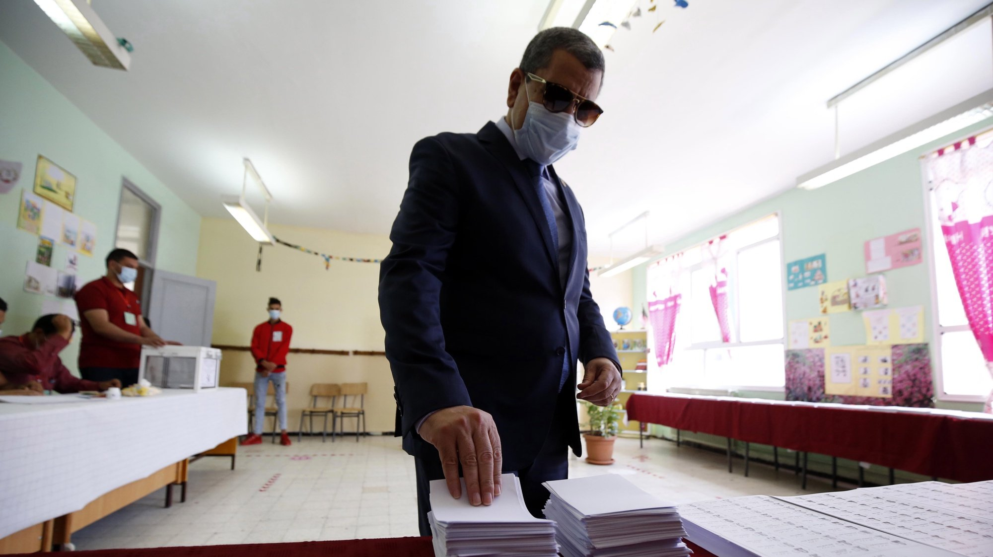 epaselect epa09264025 Algerian Prime Minister Abdelaziz Djerad picks up a ballot as he prepares to vote during parliamentary election at a polling station in Algiers, Algeria, 12 June 2021. Algeria is holding legislative elections of 2021 to elect 407 members of the lower house, the People's National Assembly (APN), for a five-year term. Initially expected for 2022, the elections are being held early in the context of a revision of the Constitution carried out by referendum in November 2020.  EPA/STRINGER