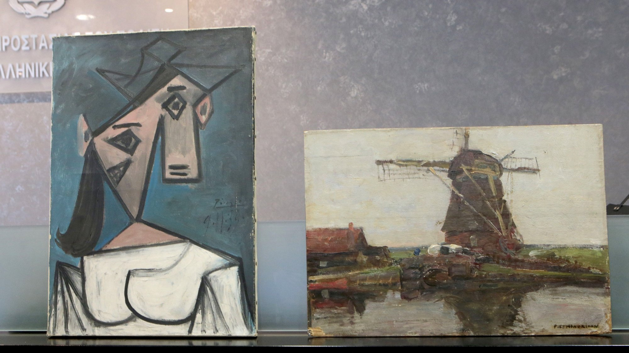 epa09310222 The stolen Picasso and Mondrian paintings, at a press conference, in Athens, Greece, 29 June 2021. The Greek police have recovered Pablo Picasso's 'Head of a Woman' and Piet Mondrian's 'Stammer Windmill', which had been stolen from the National Gallery in Athens in 2012. Police found the two paintings hidden in a gorge in Keratea, east Attica on Monday 28 June 2021. A 49-year-old man has been arrested.The perpetrators also removed an early 17th-century sketch attributed to the Italian Mannerist artist Guglielmo Caccia.  EPA/PANTELIS-SAITAS