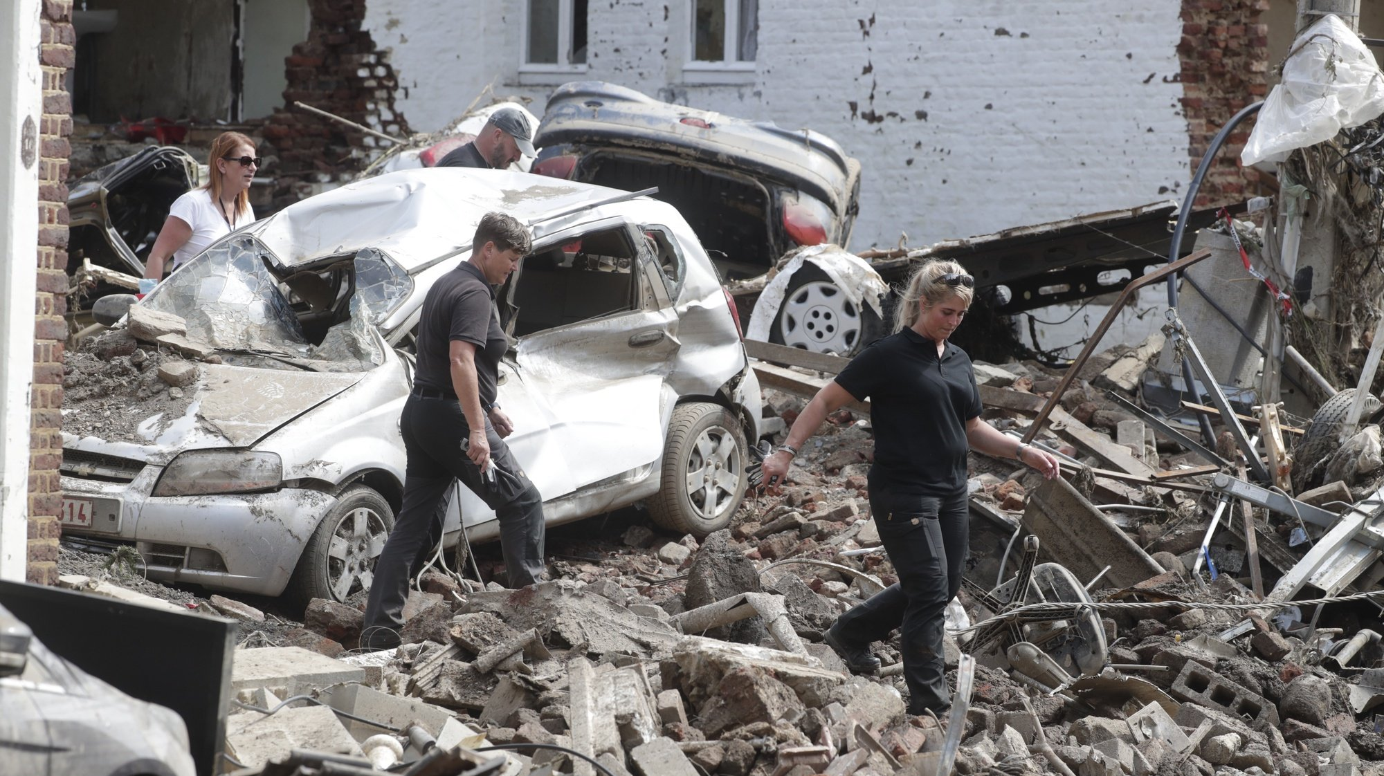 epa09353281 Members of the Belgium Federal Police with a sniffer dog search for bodies in the rubble after heavy rains caused flooding in Pepinster, Belgium, 19 July 2021. Heavy rains have caused widespread damage and flooding in parts of Belgium in the night of 14/15 July.  EPA/STEPHANIE LECOCQ