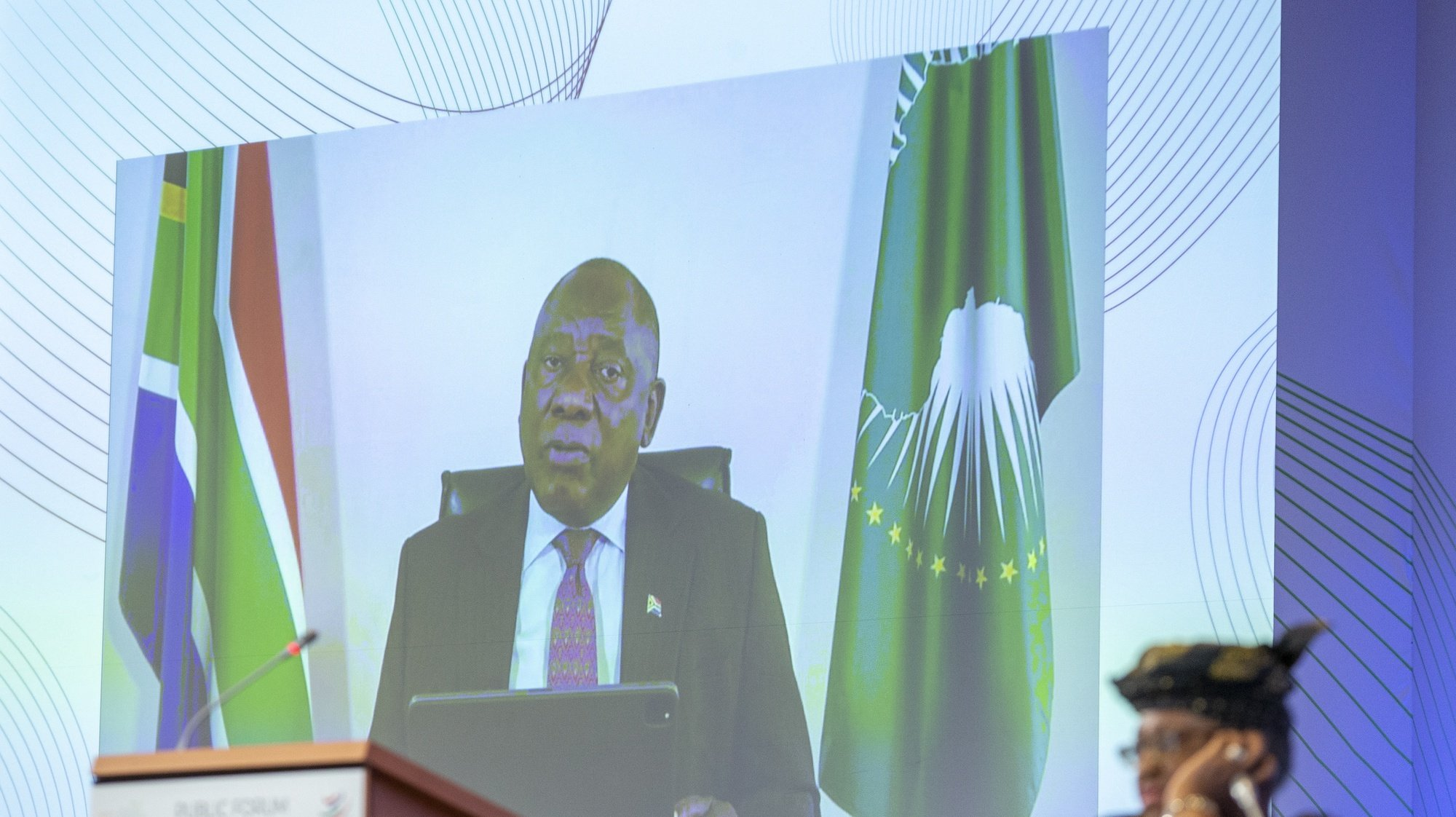 epa09492707 President of South Africa Cyril Ramaphosa is seen on a screen as he delivers his speech past Nigeria's Ngozi Okonjo-Iweala (R), Director General of the World Trade Organisation (WTO), during the opening of the WTO Forum Public on Trade Beyond COVID-19: Building Resilience, at the headquarters of the World Trade Organization (WTO) in Geneva, Switzerland, 28 September 2021.  EPA/SALVATORE DI NOLFI
