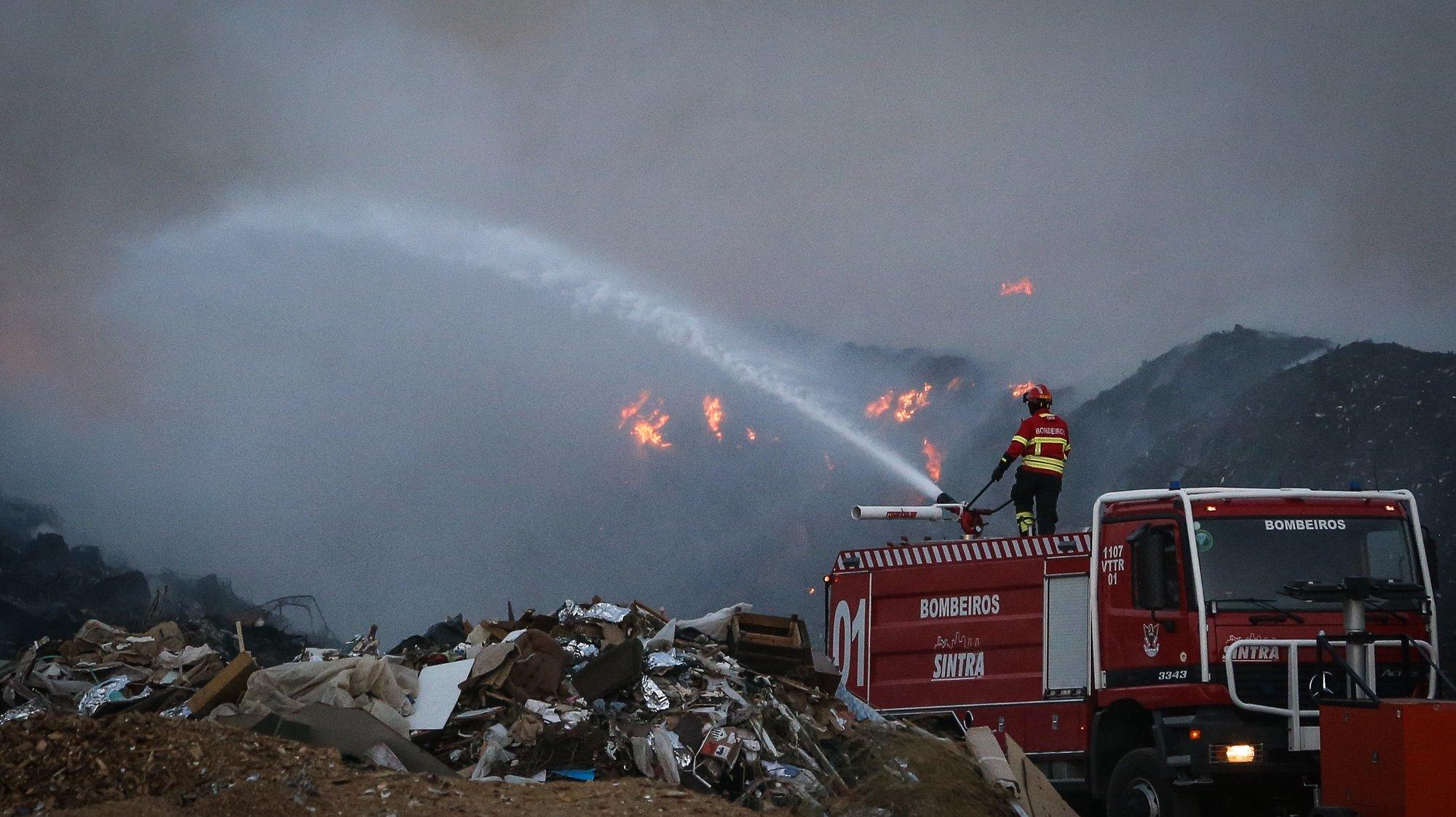 Um bombeiro combate um incêndio que deflagrou hoje à tarde na empresa Tratolixo, em Trajouce, no concelho de Cascais, 10 de julho de 2021. De acordo com fonte do Comando Distrital de Operações de Socorro (CDOS) de Lisboa, o alerta para o fogo na empresa de tratamento de resíduos sólidos Tratolixo, que entretanto se estendeu a uma zona de mato, foi dado às 16:15 e às 20:30 segundo a Autoridade Nacional de Emergência e Proteção Civil estão no terreno 154 operacionais , apoiados por 56 veículos. RODRIGO ANTUNES/LUSA
