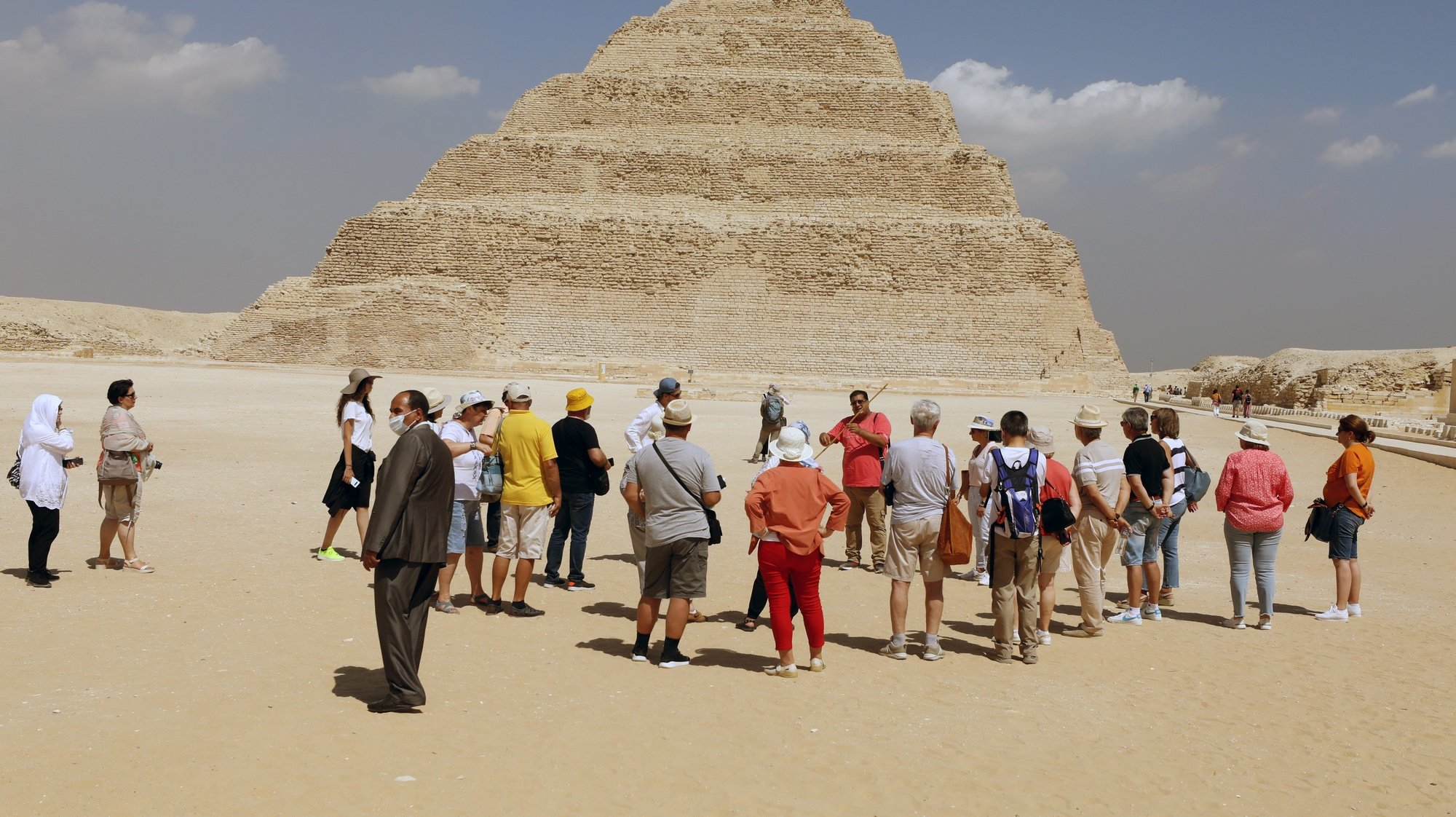 epa09467606 A group of tourists gathers outside Tomb of King Djoser step pyramid, that was reopened for visitors after a restoration, in the Saqqara area, near Giza, Egypt, 14 September 2021. An information plate by the Ministry of Tourism & Antiques at the entrance of the site describes the ancient Southern Tomb step pyramid, also known as the Saqqara pyramid, as being 'the oldest stone building of the ancient world' which was 'discovered by the English archaeologist Cecil Malaby Firth in 1928.' A series of corridors with even some false doors are described as the 'most important architectual and decorative elements' in the tomb that also features a 7.5 x 7.5m burial chamber at a depth of some 31 meters with a sarcophagus made of 16 blocks of pink granite and a height of about 3.6 meters.  EPA/KHALED ELFIQI  HANDOUT EDITORIAL USE ONLY/NO SALES