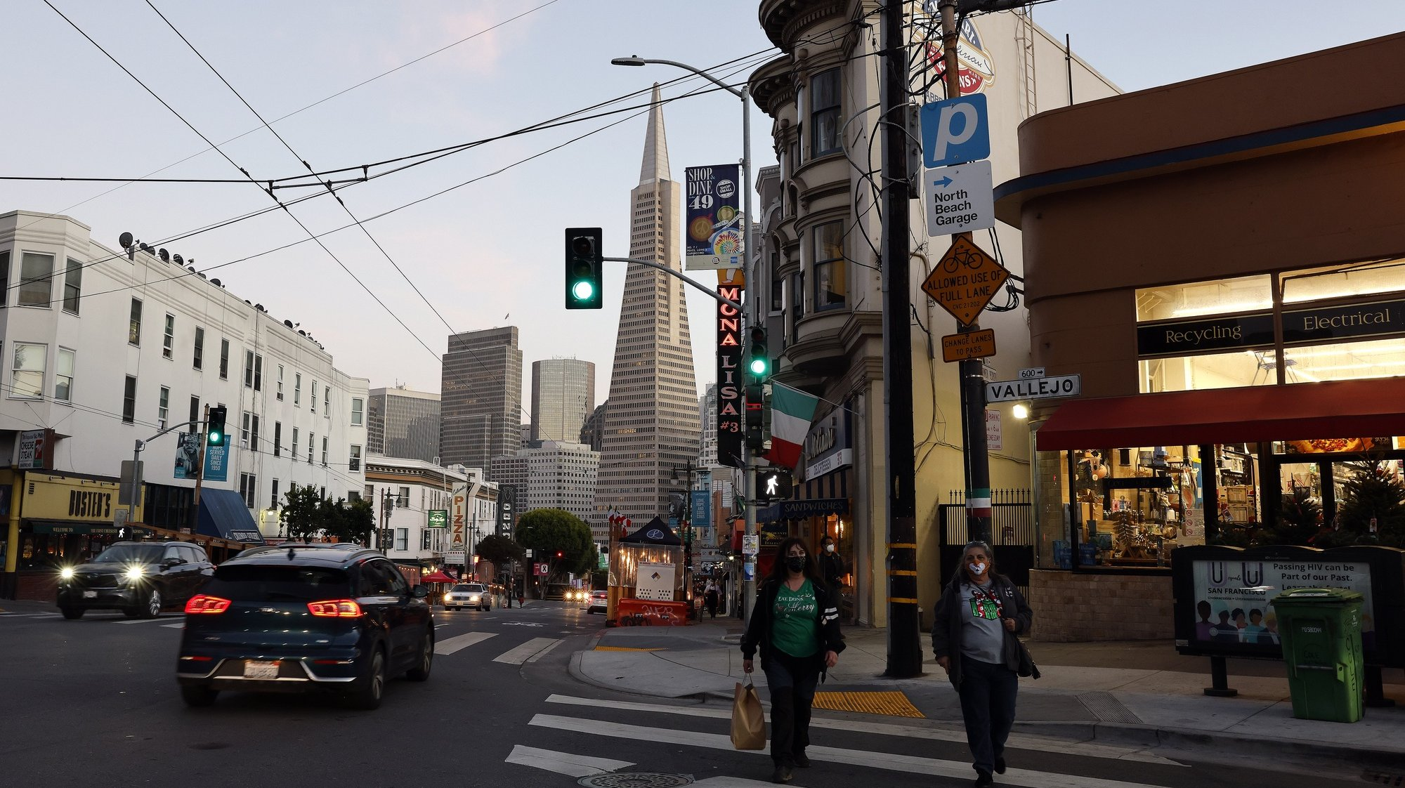 epa08853920 Pedestrians walk across a street in North Beach, as the Transamerica Pyramid building looms in the background, in San Francisco, California, USA, 30 November 2020. San Francisco is preparing for the most restrictive COVID-19 reopening tier (Purple), joining other Bay Area counties in a California curfew prohibiting non-essential business and personal gatherings from 10pm to 5am to help stop the spread the coronavirus, as the state is seeing the high rates of positive cases and hospitalizations.  EPA/JOHN G. MABANGLO