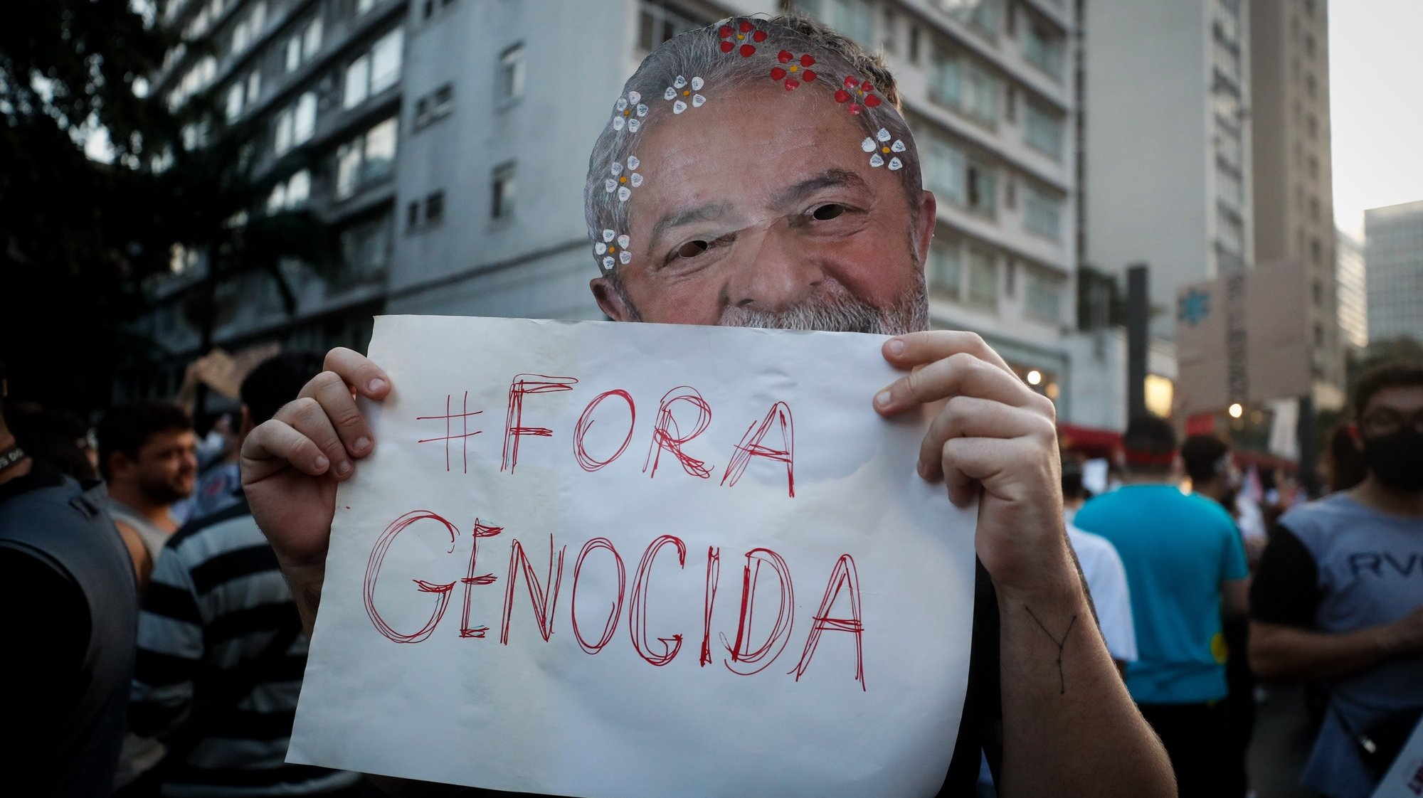 epa09236293 A man wearing a mask of former Brazilian President Luiz Inacio Lula da Silva holds a placard reading '#Out, Genocidal' during a protest against Brazilian President Jair Bolsonaro and his handling of the COVID-19 pandemic crisis, in Sao Paulo, Brazil, 29 May 2021.  EPA/Fernando Bizerra