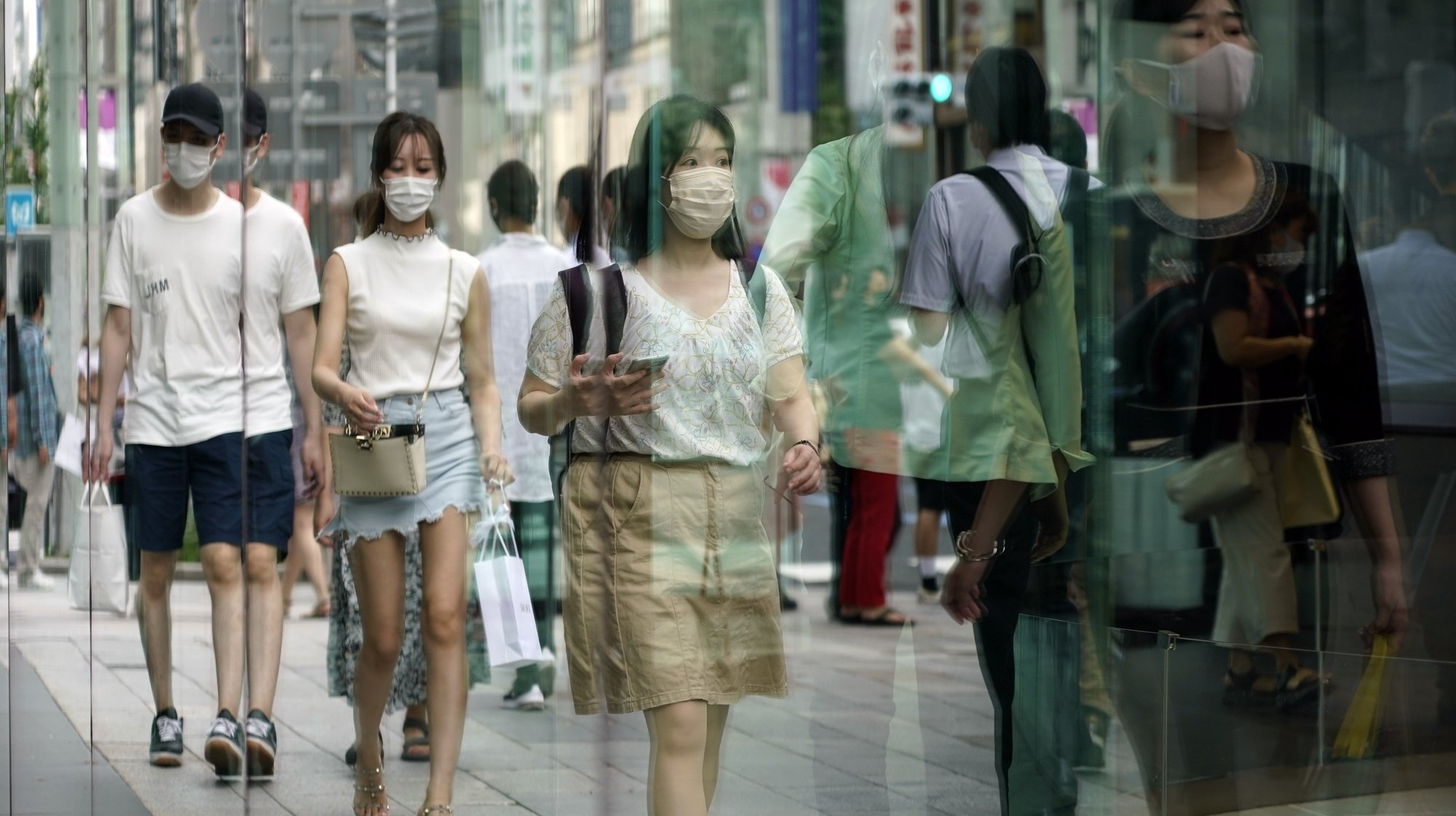 epa09376457 Passersby wearing face masks are reflected in a display window at Ginza shopping district in Tokyo, Japan, 29 July 2021. Japan's total COVID-19 new cases crossed the 10,000 mark for the first time as Tokyo records a surge of infections.  EPA/FRANCK ROBICHON