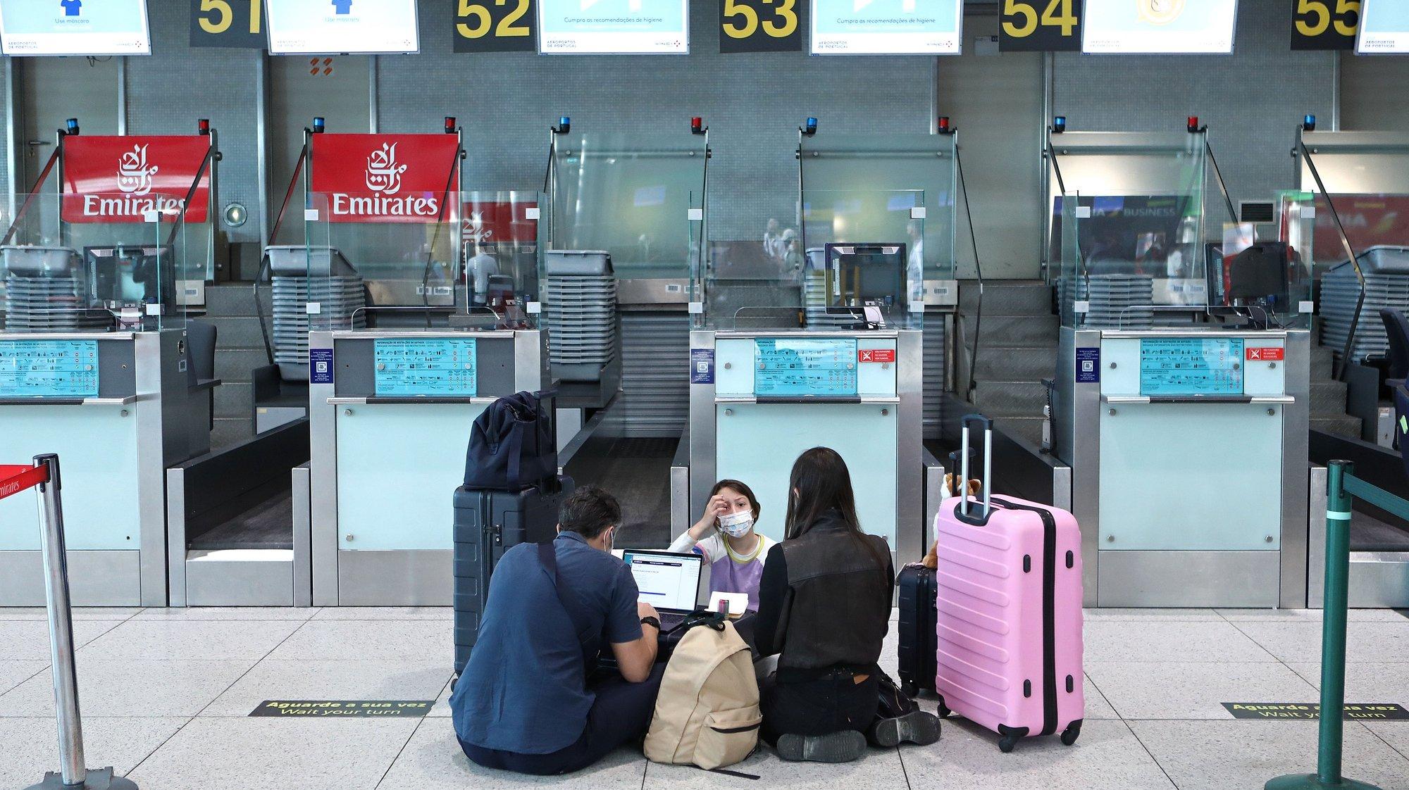 """Passageiros aguardam a sua vez para efetuar o check-in no aeroporto Humberto Delgado, no dia da entrada em vigor do certificado sanitário europeu, em Lisboa, 01 de julho de 2021. Este 'livre-trânsito' facilita a livre circulação na União Europeia no contexto da pandemia, sendo considerado um elemento fundamental para ajudar à recuperação económica da Europa no contexto da crise pandémica, designadamente para que o """"turismo possa ser uma fonte de reanimação da economia este verão"""". ANTÓNIO PEDRO SANTOS/LUSA"""