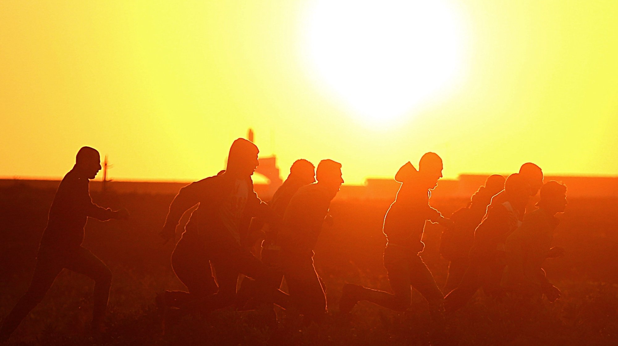 epa05074391 Palestinian youths run for cover at sunset during clashes with Israeli troops along the border between Israel and Gaza Strip in eastern Gaza, 18 December 2015.  EPA/MOHAMMED SABER