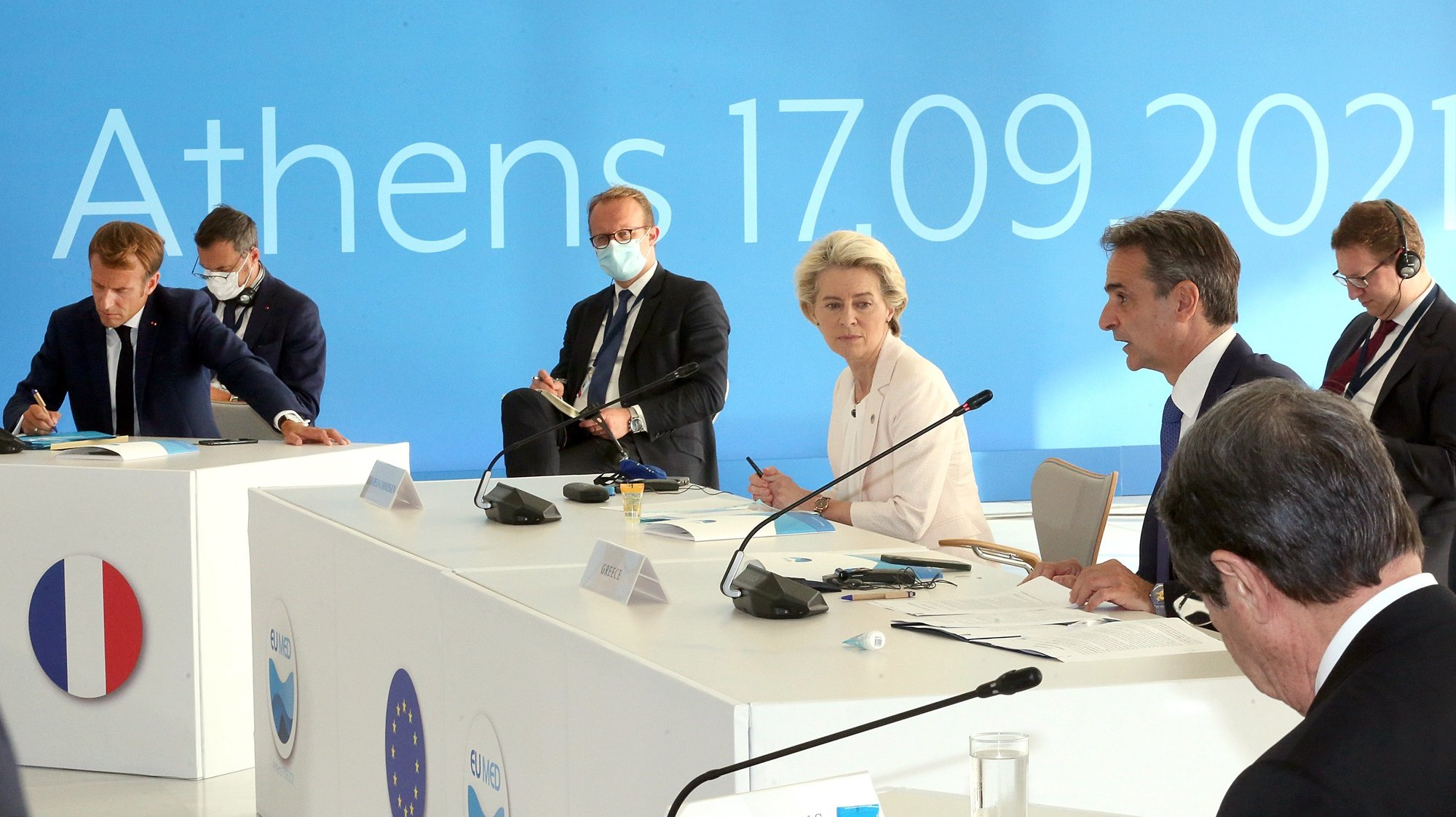 epa09473758 Greek Prime Minister Kyriakos Mitsotakis (R), President of the European Commission Ursula von der Leyen (R2) and French President Emmanuel Macron (L) participate at the EUMed9 Summit, in Athens, Greece, 17 September 2021.The agenda of the Summit, which acquires special geopolitical weight, includes security challenges in the Mediterranean that endanger stability in the region, potential new crises, such as the threat of migration flows after the latest developments in Afghanistan, and other crises, the consequences of which Mediterranean countries are already experiencing, such as climate change.  EPA/ORESTIS PANAGIOTOU