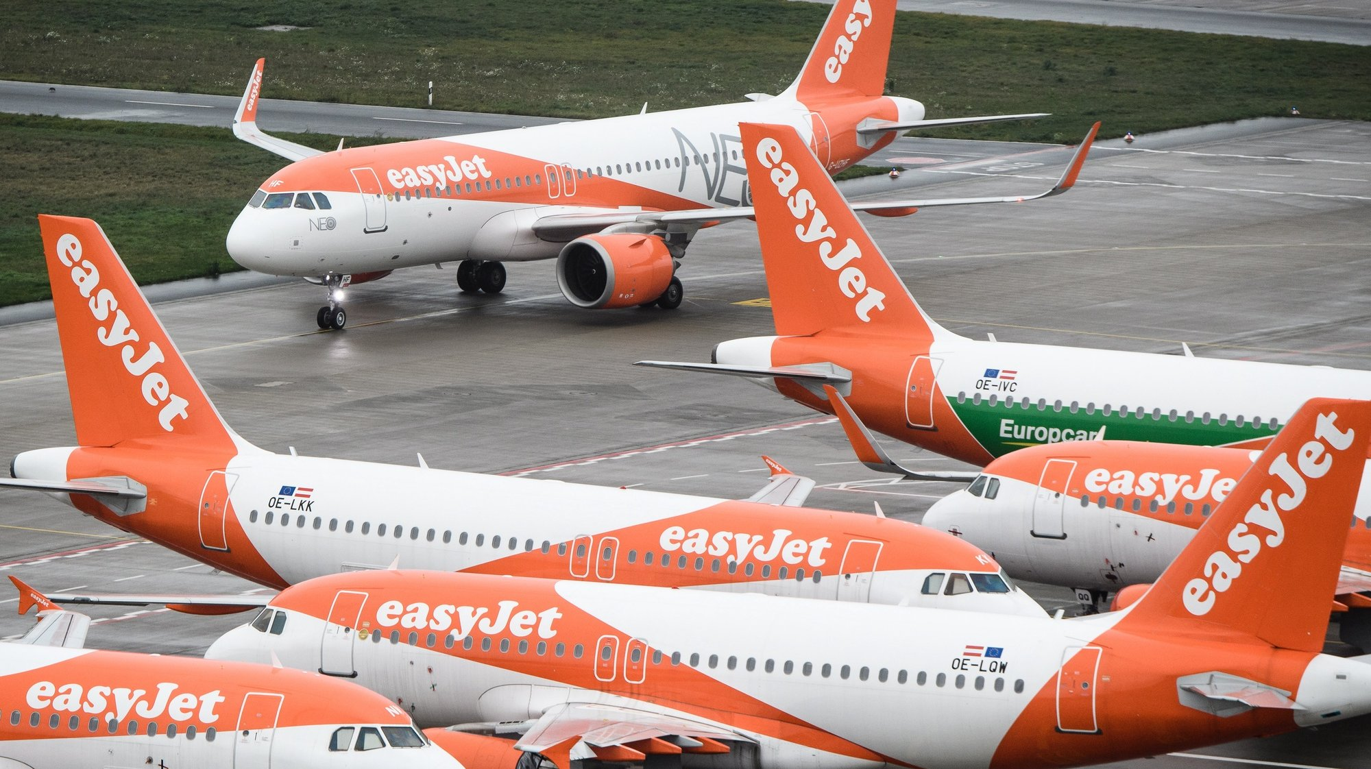 epa08967940 (FILE) - An EasyJet plane (top), taxiing on the tarmac during the opening of BER Berlin Brandenburg Airport in Schoenefeld, Germany, 31 October 2020 (reissued 27 January 2021). EasyJet is due to publish their quarterly results 27 January 2021 while according to media reports analysts forecast easyjet's revenue may have dropped up to 80 per cent from same period in 2020.  EPA/CLEMENS BILAN / POOL *** Local Caption *** 56465488