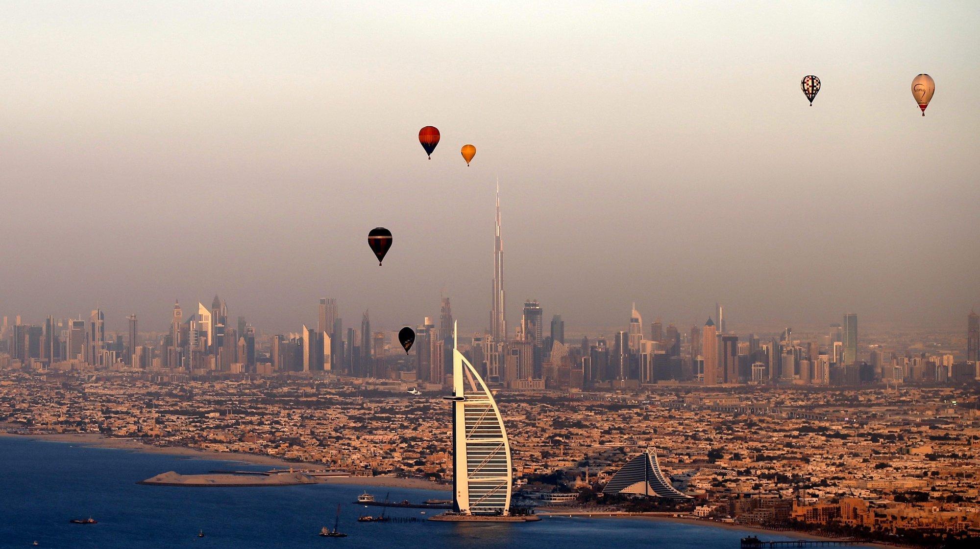 epaselect epa05066387 Hot Air Aerostats fly over the luxury hotel of Burj Al-Arab during Dubai International Balloon Fiesta as part of the last day of Dubai Air Games 2015 in Gulf emirate of Dubai, United Arab Emirates, 12 December 2015.  EPA/ALI HAIDER