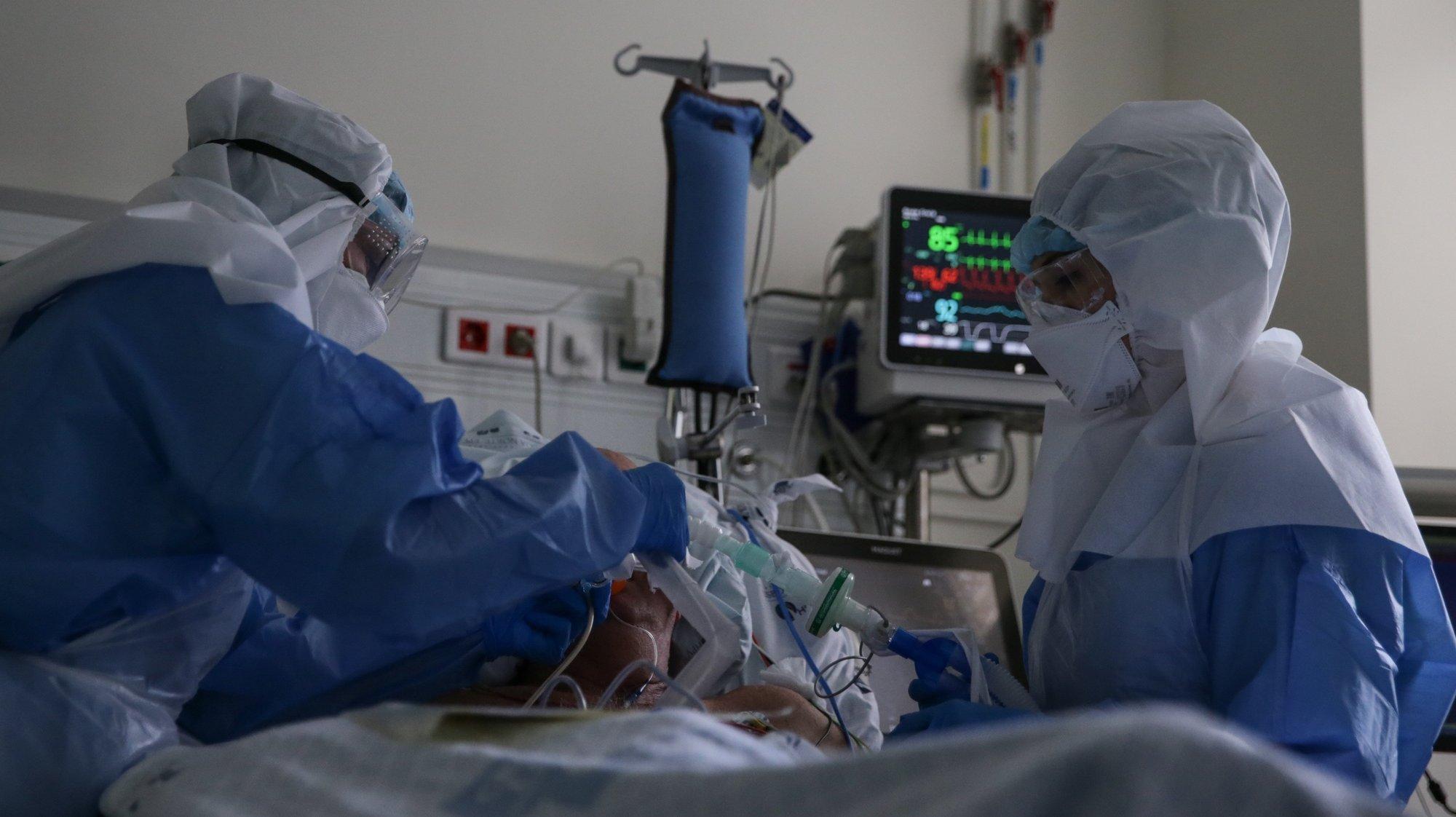Enfermeiras cuidam de um paciente hospitalizado na Unidade de Cuidados Intensivos Covid 19 do Hospital Santa Maria em Lisboa, 27 de outubro de 2020. A urgência dedicada aos casos suspeitos de covid-19 do Hospital Santa Maria, em Lisboa, reflete a evolução da pandemia em Portugal com doentes a avolumarem-se à porta para realizar o teste e no interior a capacidade quase esgotada. O medo de perder o emprego leva muitos doentes com covid-19 a esconderem que estão infetados e a continuar a trabalhar, disseminando a doença que, nesta fase, começa a ser um caso também social e que leva a muitos internamentos no Santa Maria. (ACOMPANHA TEXTO DA LUSA DE 30 DE OUTUBRO DE 2020) TIAGO PETINGA/LUSA