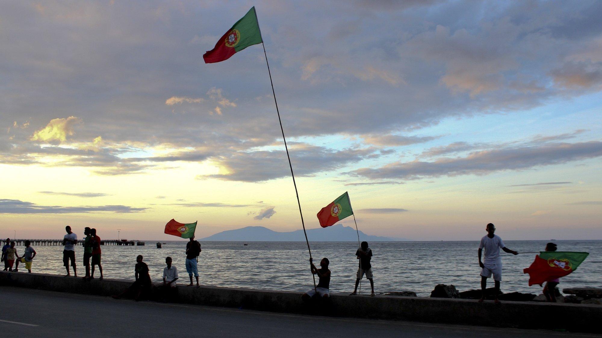 Timorenses empunham bandeiras de Portugal, no dia em que a seleção nacional de futebol portuguesa se estreia no Mundial2014 de futebol, no jogo do Grupo G contra a Alemanha, em Díli, Timor-Leste, 16 de junho de 2014. (ACOMPANHA TEXTO). ANTÓNIO AMARAL/LUSA
