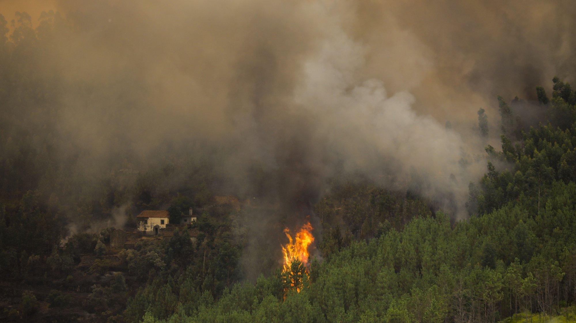 """As chamas aproximam-se das casas durante o incêndio no distrito de Castelo Branco que está a ser combatido em quatro setores, estando os situados a norte """"mais estabilizados"""", de acordo com o comandante, e os a sul """"mais ativos"""", num total de três frentes ativas, Oleiros, 26 de julho de 2020. No terreno estavam cerca de 744 operacionais apoiados por 232 veículos, 12 meios aéreos e nove máquinas de rasto. PAULO CUNHA /LUSA"""