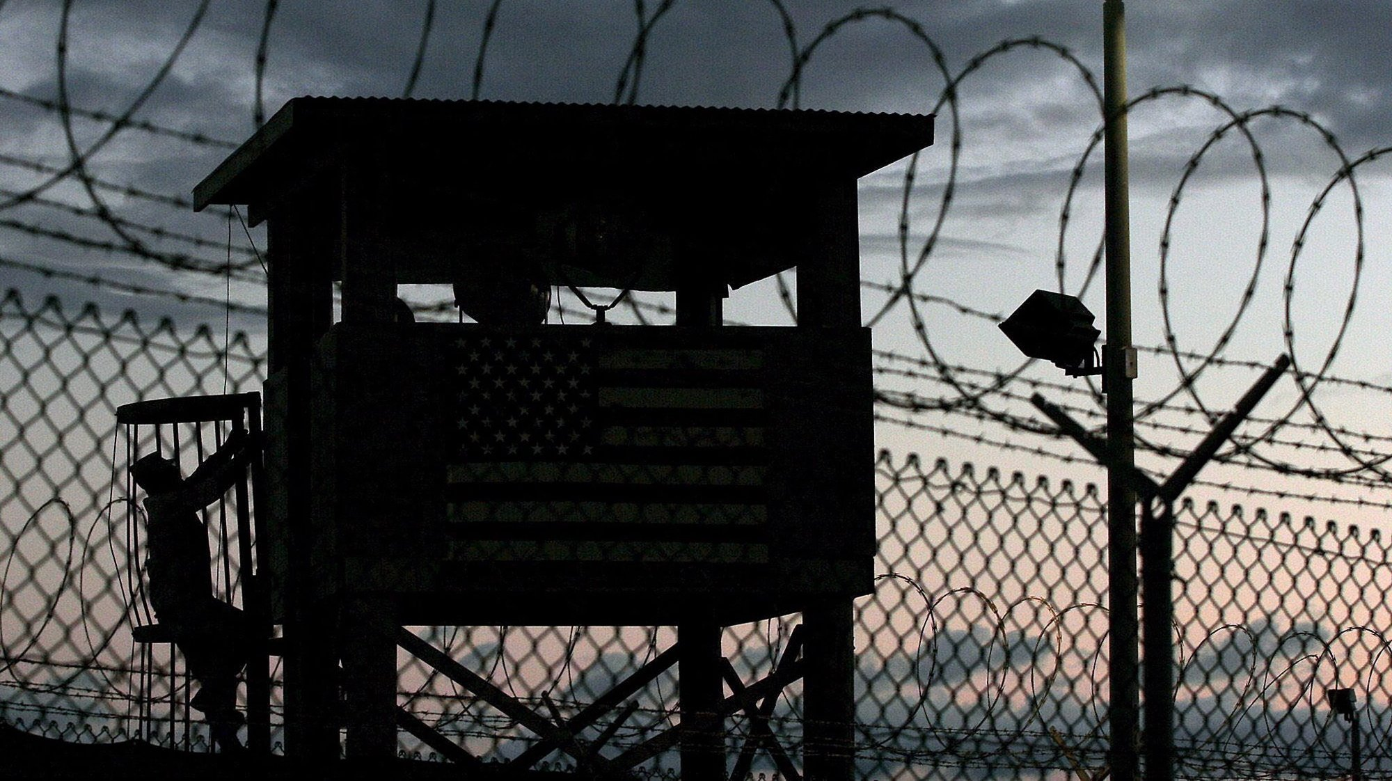 epa05488797 (FILE) A file picture dated 16 February 2006 shows a Joint Task Force member (L, silhouetted) climbing to his guard tower post surrounded by triple rows of razor barbed wire that perimeter the security of Camp Delta, Guantanamo Naval Sation, Cuba. According to media reports on 16 August 2016, the US has sent 15 Guantanamo Bay (GTMO) inmates, 12 Yemenis and three Afghanis, to the United Arab Emirates (UAE). The transfer, the largest under US president Barack Obama's administration, has brought the total number of prisoners in the US military prison down to 61, media added quoting the Pentagon.  EPA/JOHN RILEY