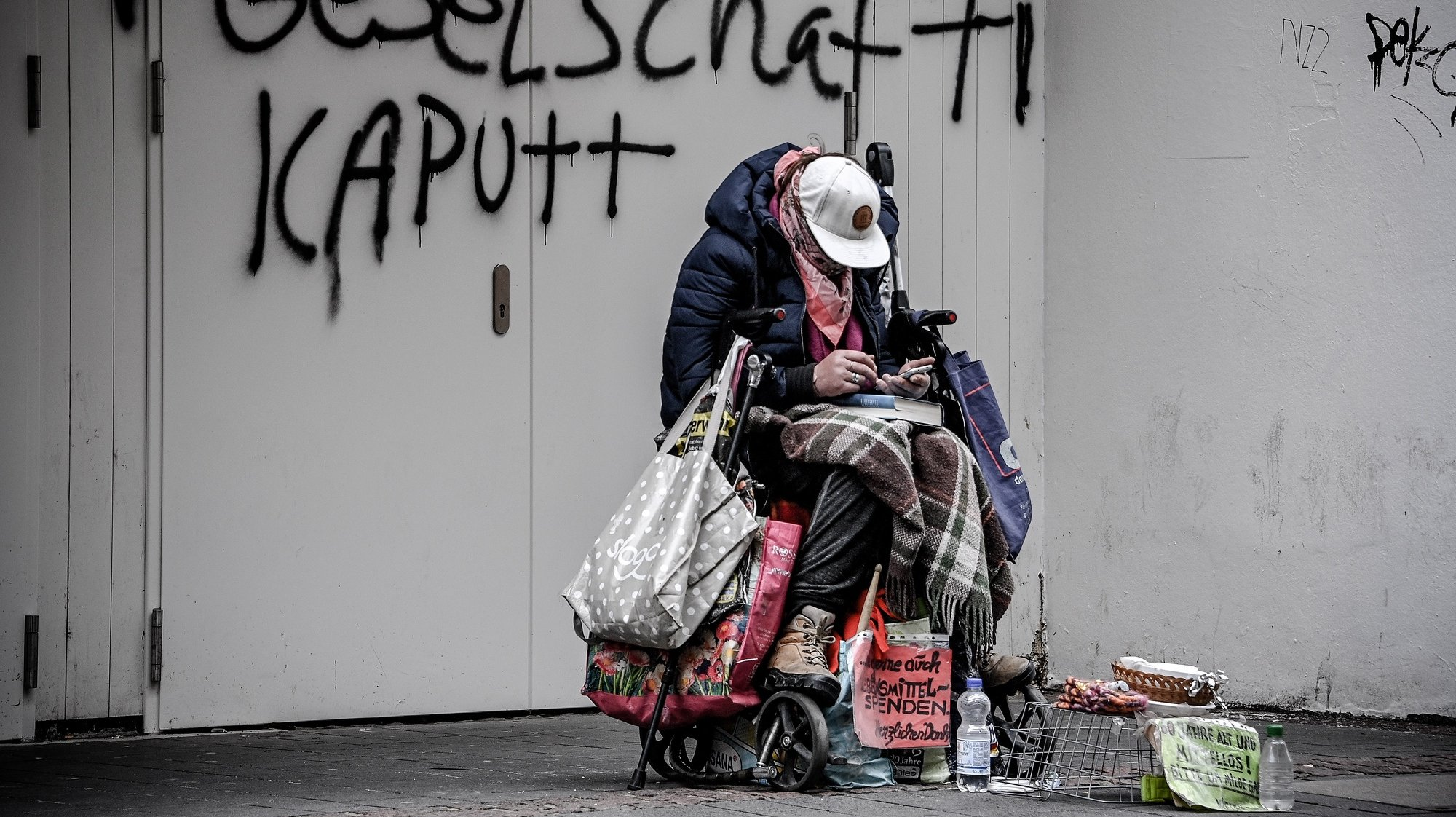epaselect epa09069914 A homeless person sits huddled in front of a wall on which the words 'broken society' are spray-painted, in Bonn, Germany, 12 March 2021. In Germany, many stores that had been closed for months are opening again. Shopping in stores is possible again, but must be well planned. Anyone who wants to look for clothes, shoes, electrical goods or furniture again on site must book a time slot in advance. How long that is varies by store. The shopping time must be firmly limited according to the German Corona Protection Ordinance.  EPA/SASCHA STEINBACH