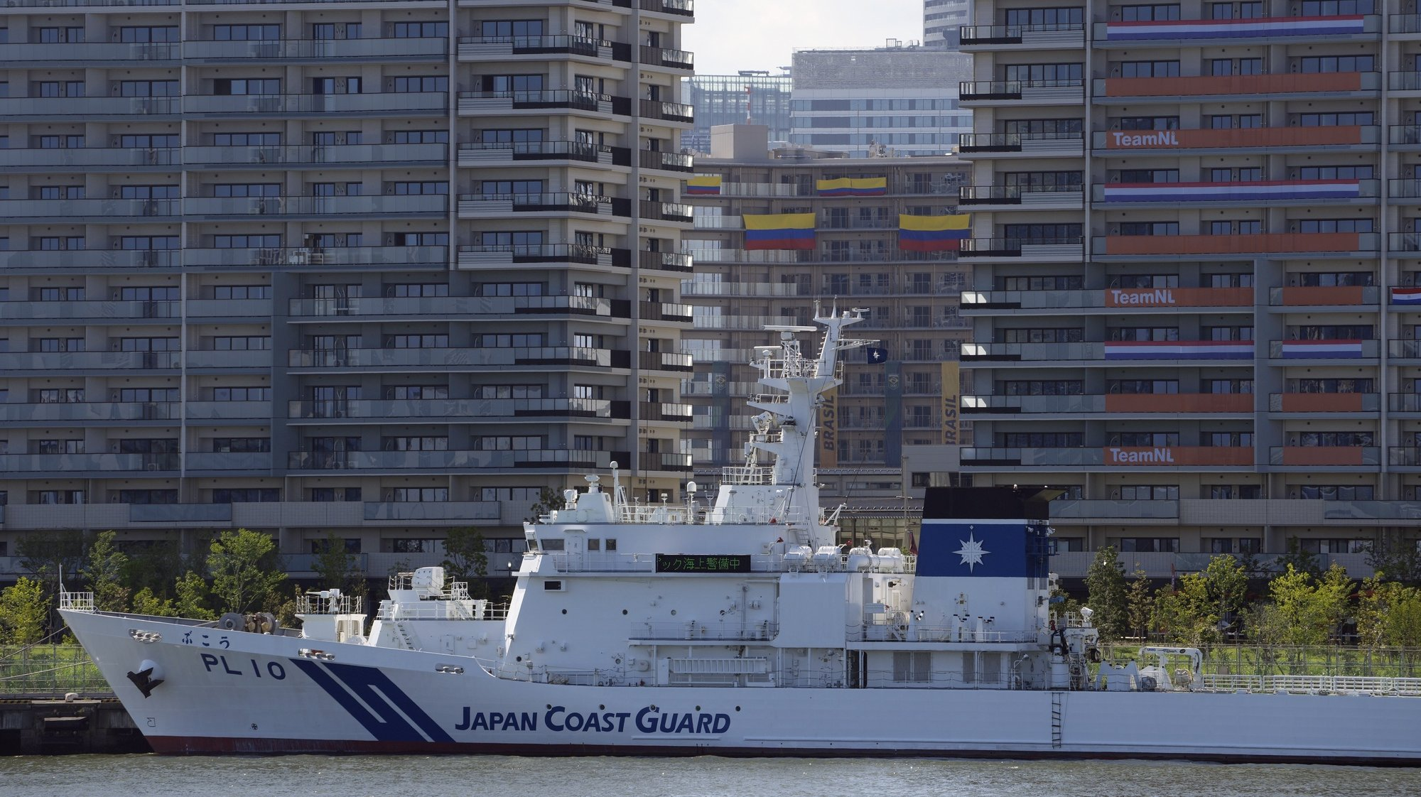 epa09349799 A Japan coast guard vessel berth before the Olympic Village buildings in Tokyo, Japan, 17 July 2021. The Tokyo Olympics organisers confirmed the first COVID-19 case in the Tokyo athletes' village less than a week before the opening of the Games.  EPA/FRANCK ROBICHON