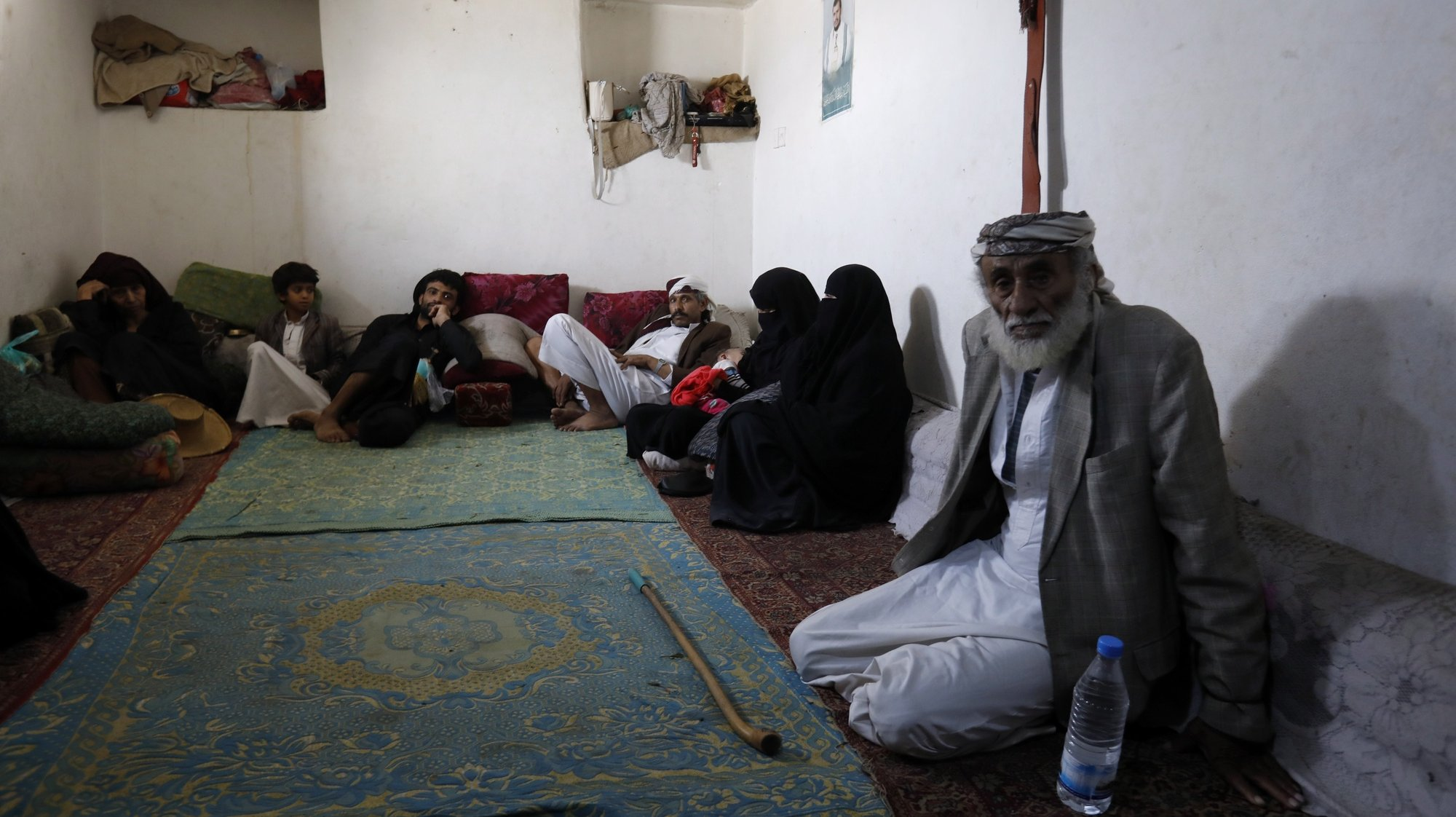 epa08495615 Yemeni displaced Mohammed Ahmed, 77, (R) and his relatives sit in a rental house in Sanaa, Yemen, 18 June 2020 (issued 19 June 2020). He says 'I have been displaced from the city of Haradh, northwestern Yemen, since 2016 due to the war that destroyed homes and roads. We displaced to Sanaa, leaving our properties there. We had no choice but to do so. We have no income except what we earn from collecting and selling plastic items. We receive a food ration from the World Food Programme once in every two months. It is not enough for a family of eight'. World Refugee Day is marked annually on 20 June. According to the UNHCR, more and more refugees today live in urban settings outside refugee camps. Some crises have lasted so long that the tent camps became built-up urban areas. While some refugees depend on international help through NGOs, others start a new life, changing everything from occupation, to social status, to adapt to their new realities.  EPA/YAHYA ARHAB  ATTENTION: This Image is part of a PHOTO SET