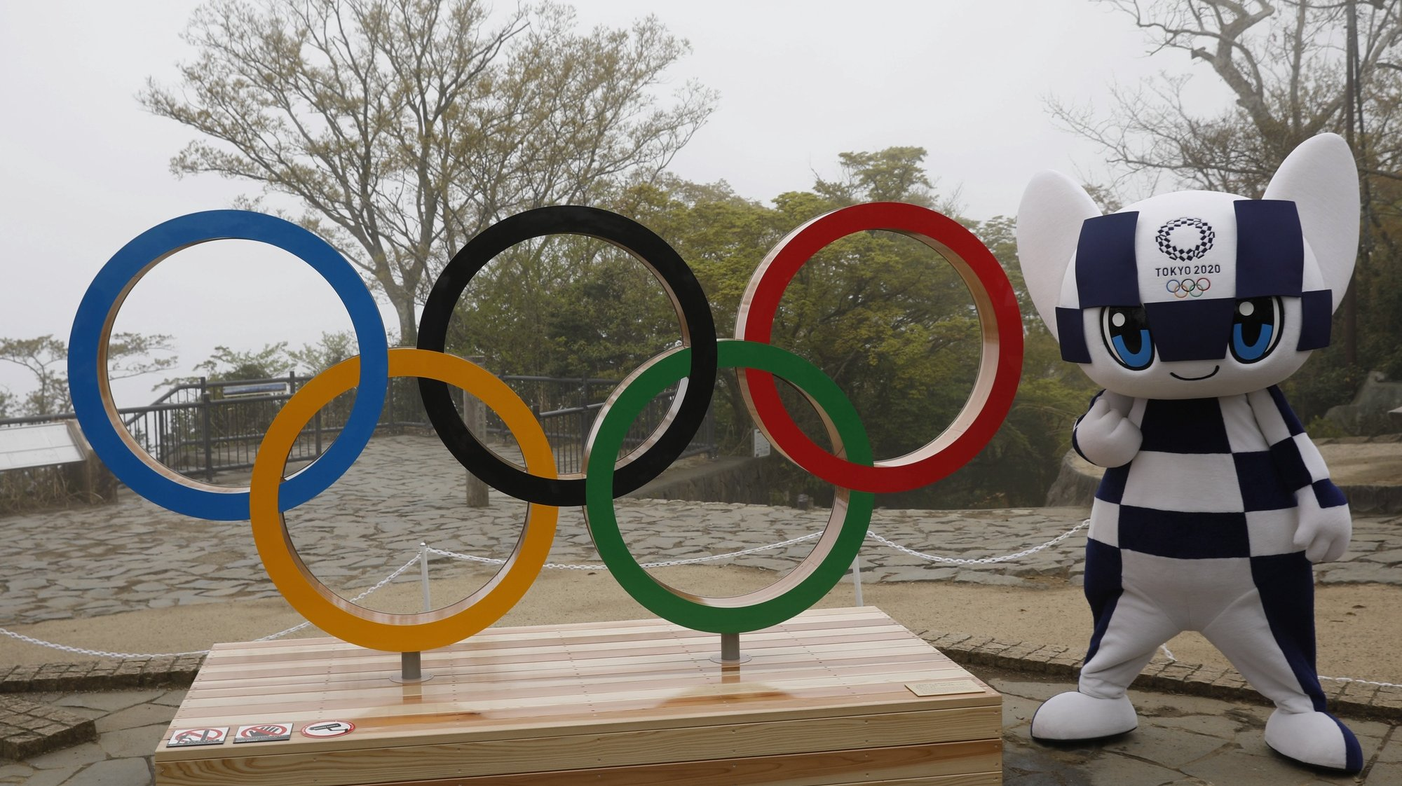 epa09134158 Tokyo 2020 Olympic Games mascot Miraitowa poses with a display of Olympic Symbol after unveiling ceremony of the symbol on Mt. Takao in Hachioji, Japan, 14 April 14, 2021, to mark 100 days before the start of 2020 Tokyo Olympic Games.  EPA/KIM KYUNG-HOON / POOL