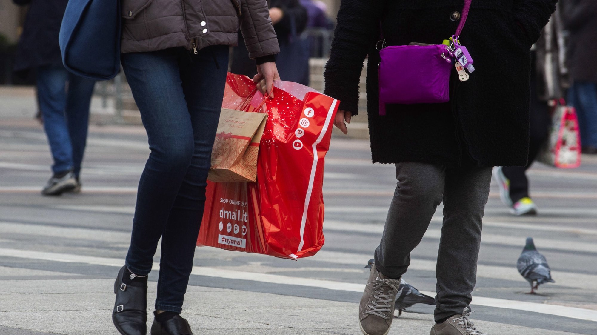 epa08890252 Shoppers walk with bags in the center of Milan as they shop ahead of the Christmas holidays in Milan, Italy, 17 December 2020.  EPA/ANDREA FASANI