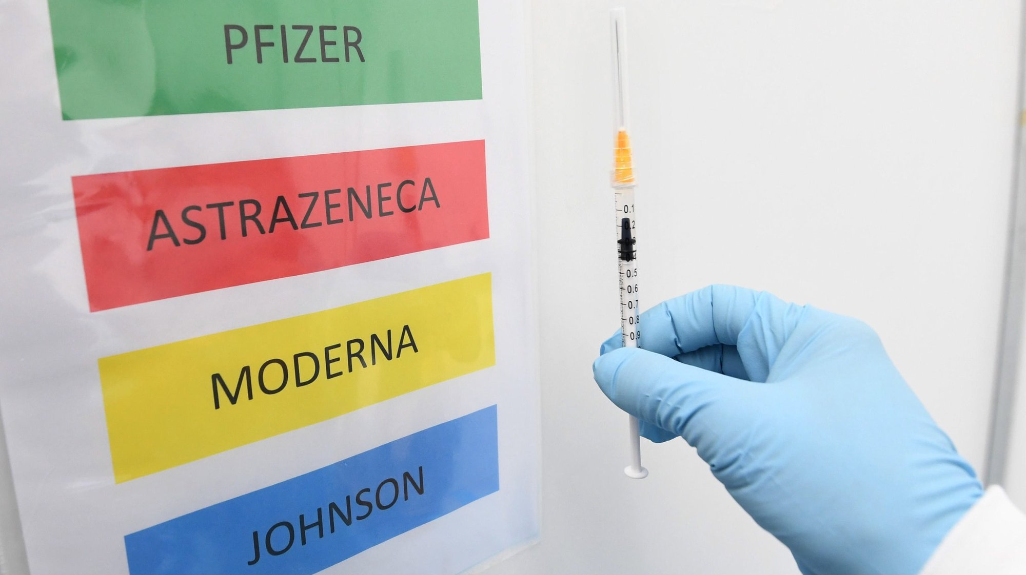 epa09170062 A medical staff holds a syringe next to a color code sign listing the Covid-19 vaccines BioNTech/Pfizer, AstraZeneca, Moderna and Johnson&Johnson at the Covid-19 vaccination hub set up in Novegro, near Milan, Italy, 30 April 2021.  EPA/Daniel Dal Zennaro