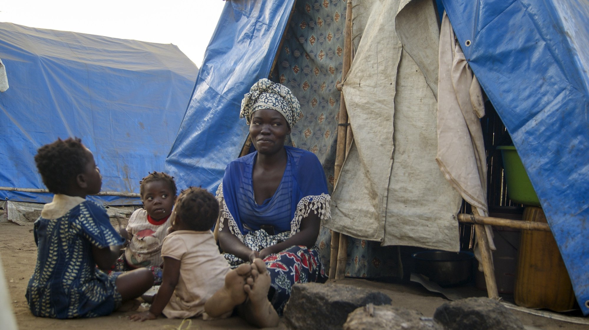 epa09417536 A woman and children in one of the shelter camps in Metuge, a space housing displaced people fleeing armed violence in northern Mozambique, Cabo Delgado, Mozambique, 16 August 2021 (issued 17 August 2021). Following the attacks, which have terrorized Cabo Delgado province since 2017, there are more than 3,100 deaths, according to the ACLED conflict registration project, and more than 817,000 displaced people, according to Mozambican authorities.  EPA/LUISA NHANTUMBO