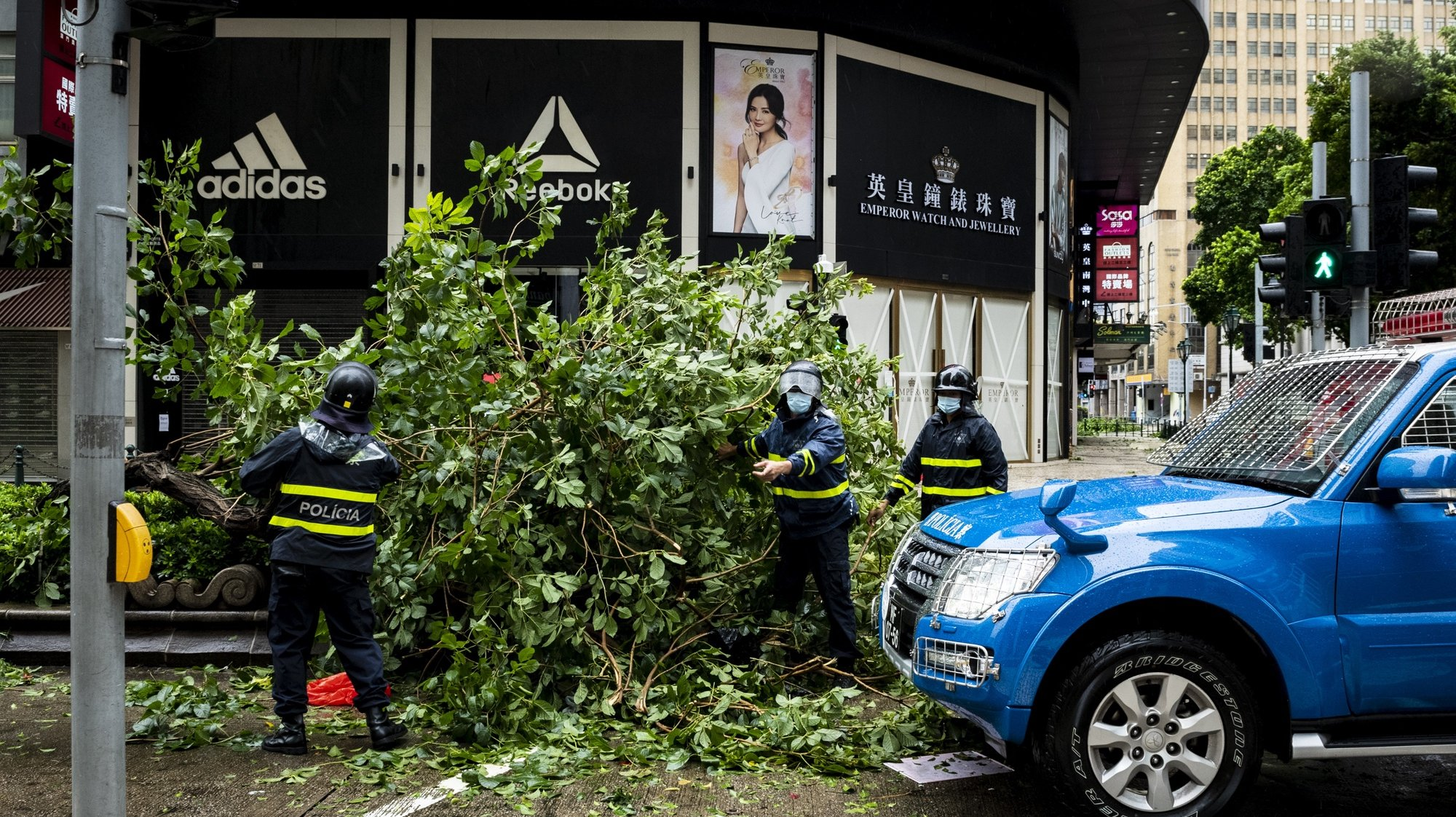 epa08612362 City workers remove an uprooted tree after Tropical storm Higos had passed very close to Macao, China, 19 August 2020. Higos is now 100 kilometers northwest of Macau and 'is gradually moving away' from the territory.  EPA/TATIANA LAGES