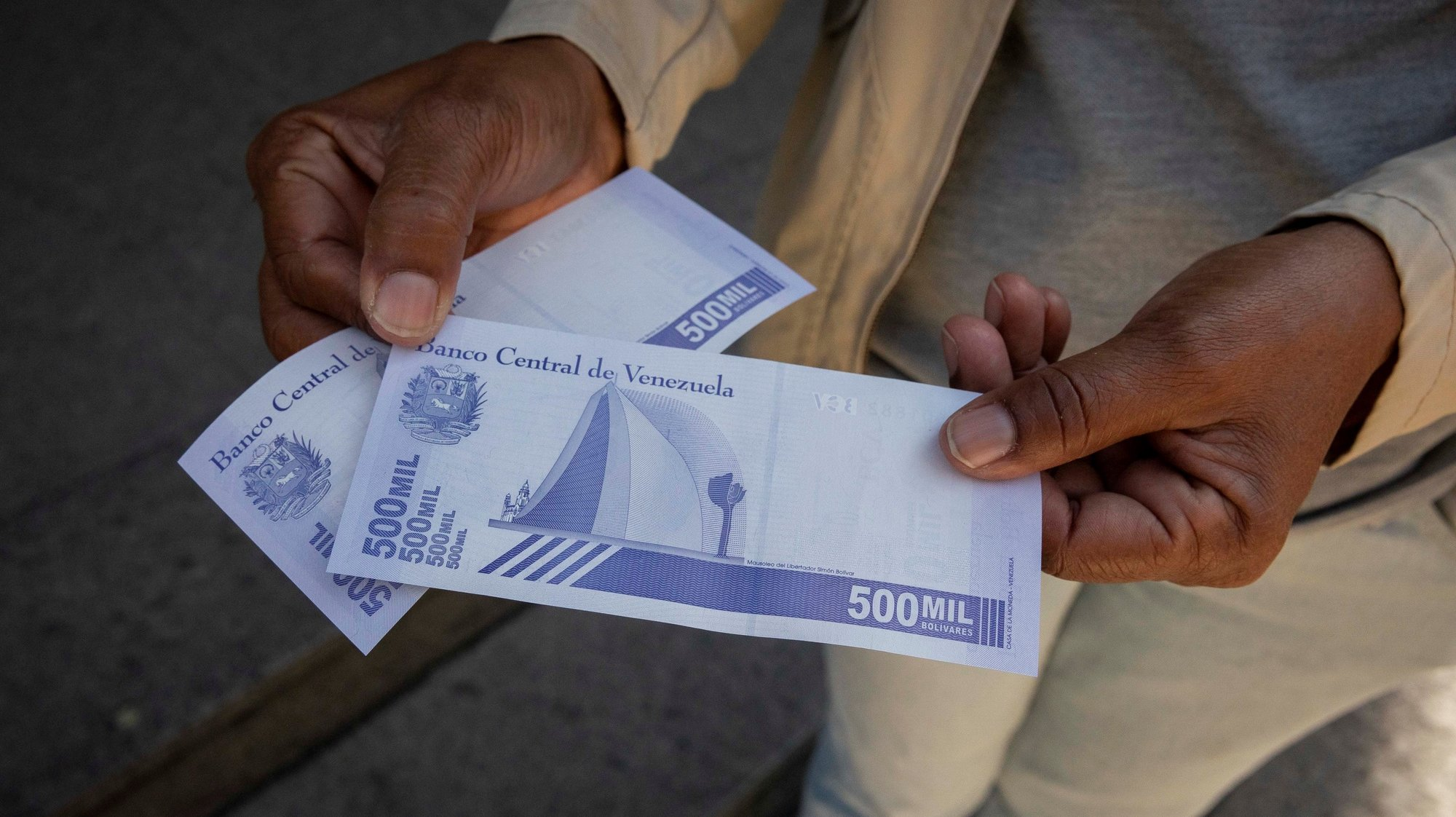 epa09084341 A person shows the new 500,000 bolivar notes, in Caracas, Venezuela, 15 March 2021 (reissued 19 March 2021). Venezuela, which is hit by high hyperinflation and US sanctions, has introduced a new 1,000,000 bolivar note alongside a 200,000 and a 500,000 note. The 1 million bill equals around 0,47 euro, which Venezuelans complain won't buy them much, recalling that the bolivar already lost eight zeros in the past two currency reconversions.  EPA/Rayner Pena