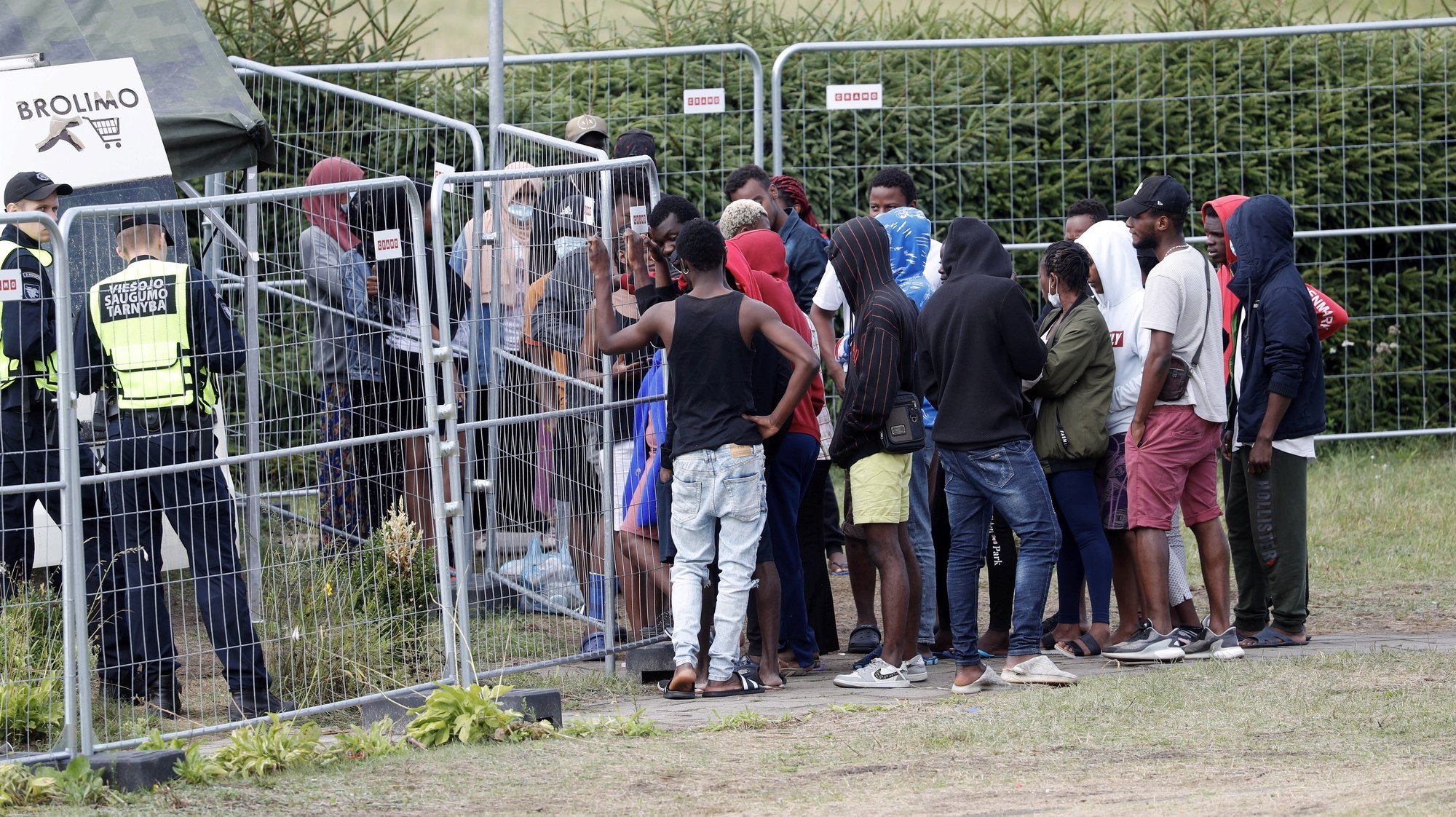 epa09388795 Detained migrants waiting in line for buying goods from an off-site store in a car at the migrant detention centre in Vydeniai, Lithuania, 02 August 2021. Some 3,800 migrants were detained in Lithuania in 2021 so far and officials have accused the Belarus regime to be behind an increased number of migrants crossing into Lithuania.  EPA/TOMS KALNINS
